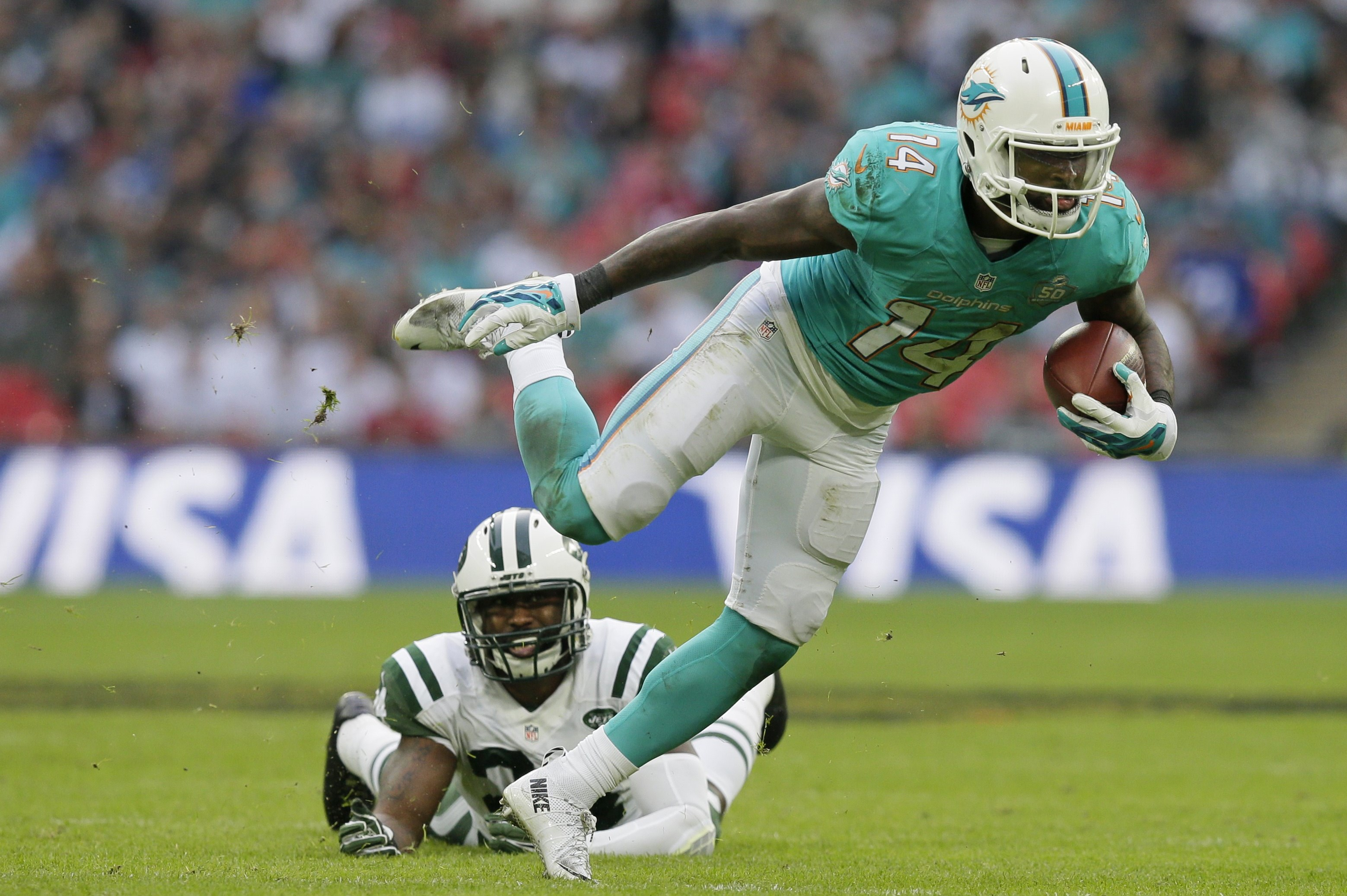 FILE - In this Oct. 4, 2015, file photo, Miami Dolphins' Jarvis Landry breaks the challenge from New York Jets' Darrelle Revis during an NFL football game at Wembley stadium in London. Former LSU teammates Odell Beckham Jr. and Jarvis Landry are two of th