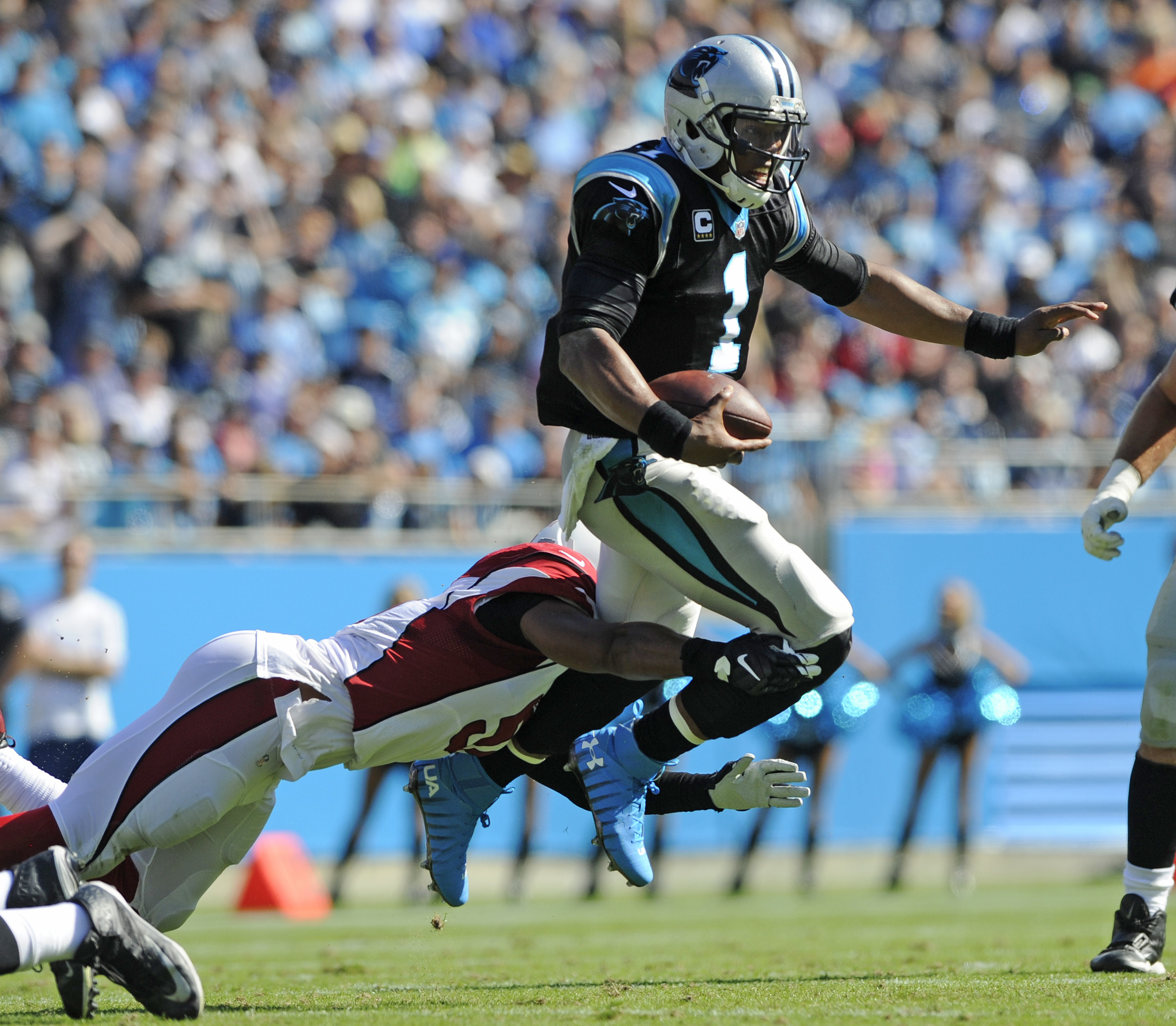 Carolina Panthers' Cam Newton (1) leaps to avoid the tackle of Arizona Cardinals' Kevin Minter (51) in the first quarter of an NFL football game in Charlotte, N.C., Sunday, Oct. 30, 2016. (AP Photo/Mike McCarn)