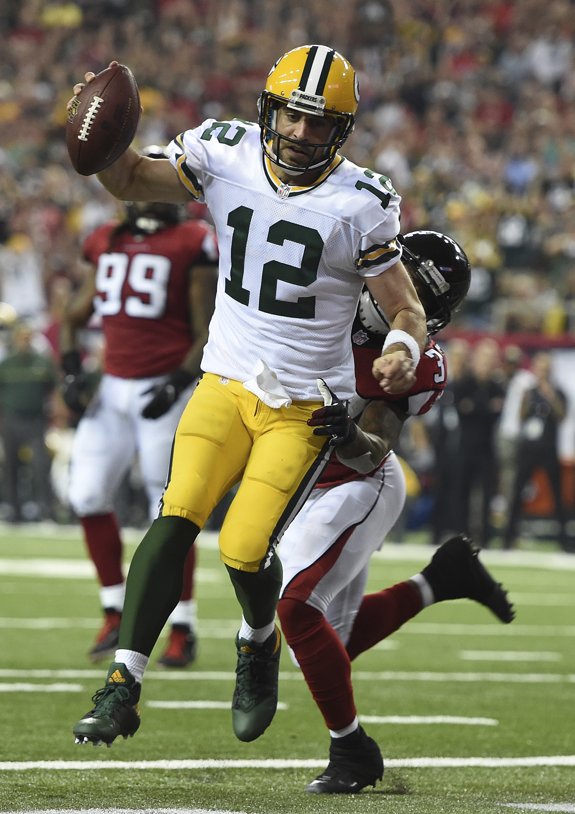 Green Bay Packers quarterback Aaron Rodgers (12) runs into the end zone for an extra point against Atlanta Falcons free safety Ricardo Allen (37) during the second of an NFL football game, Sunday, Oct. 30, 2016, in Atlanta. (AP Photo/Rainier Ehrhardt)