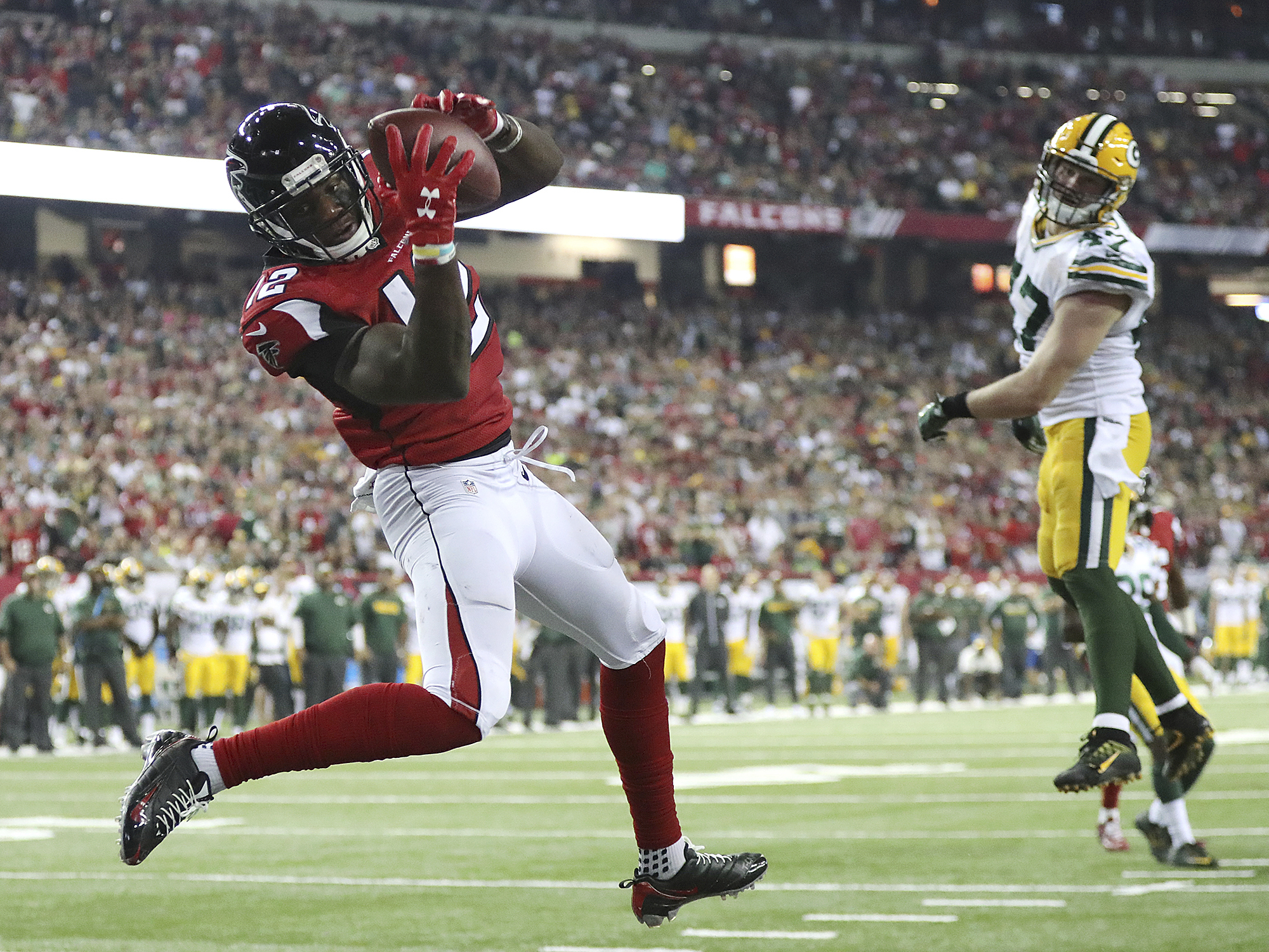 Atlanta Falcons wide receiver Mohamed Sanu catches a touchdown pass from Matt Ryan past Green Bay Packers defender Jake Ryan for a 33-32 victory in an NFL football game on Sunday, Oct. 30, 2016, in Atlanta. (Curtis Compton/Atlanta-Journal Constitution via