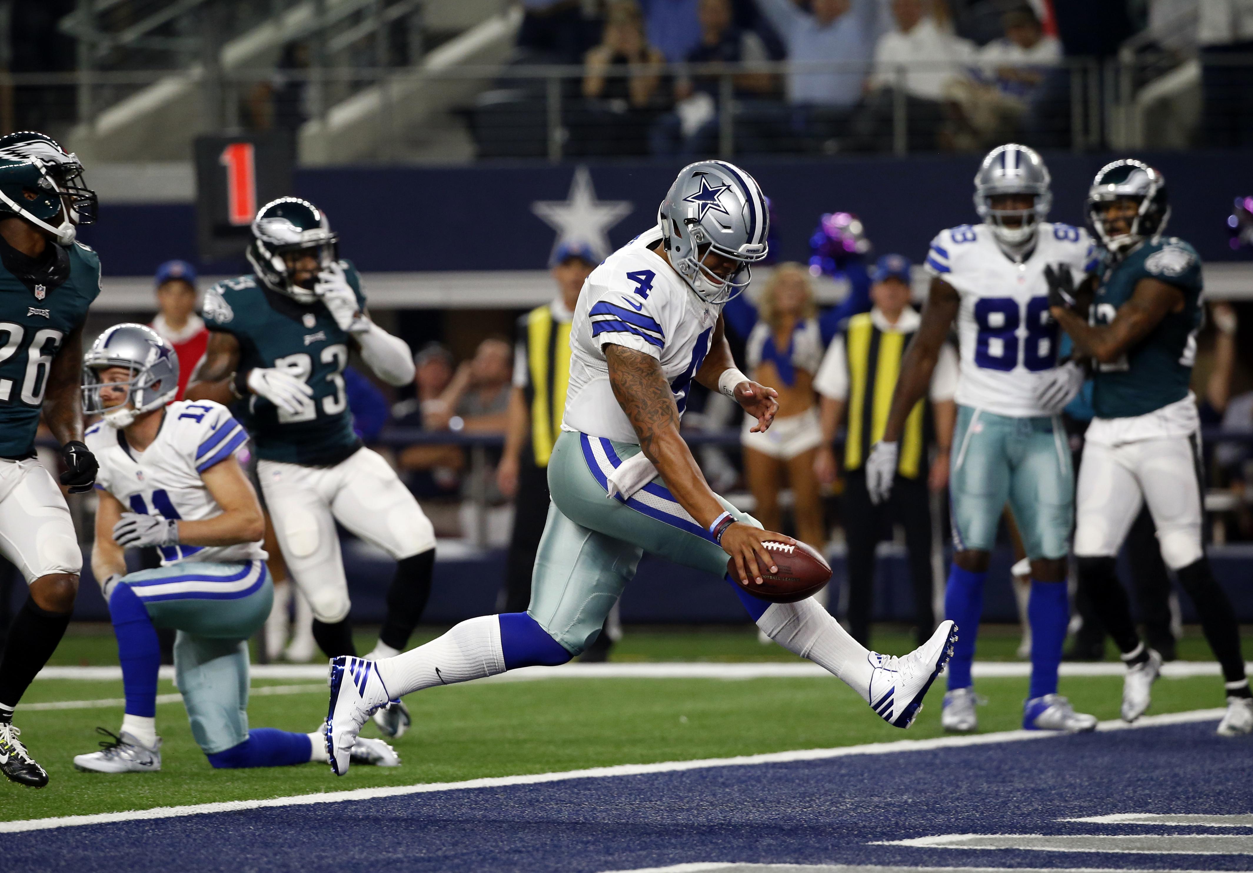 FILE - In this Sunday, Oct. 30, 2016, file photo, Dallas Cowboys quarterback Dak Prescott (4) runs the ball for a touchdown against the Philadelphia Eagles in the first half of an NFL football game in Arlington, Texas.  As Dallas rookie quarterback's winn