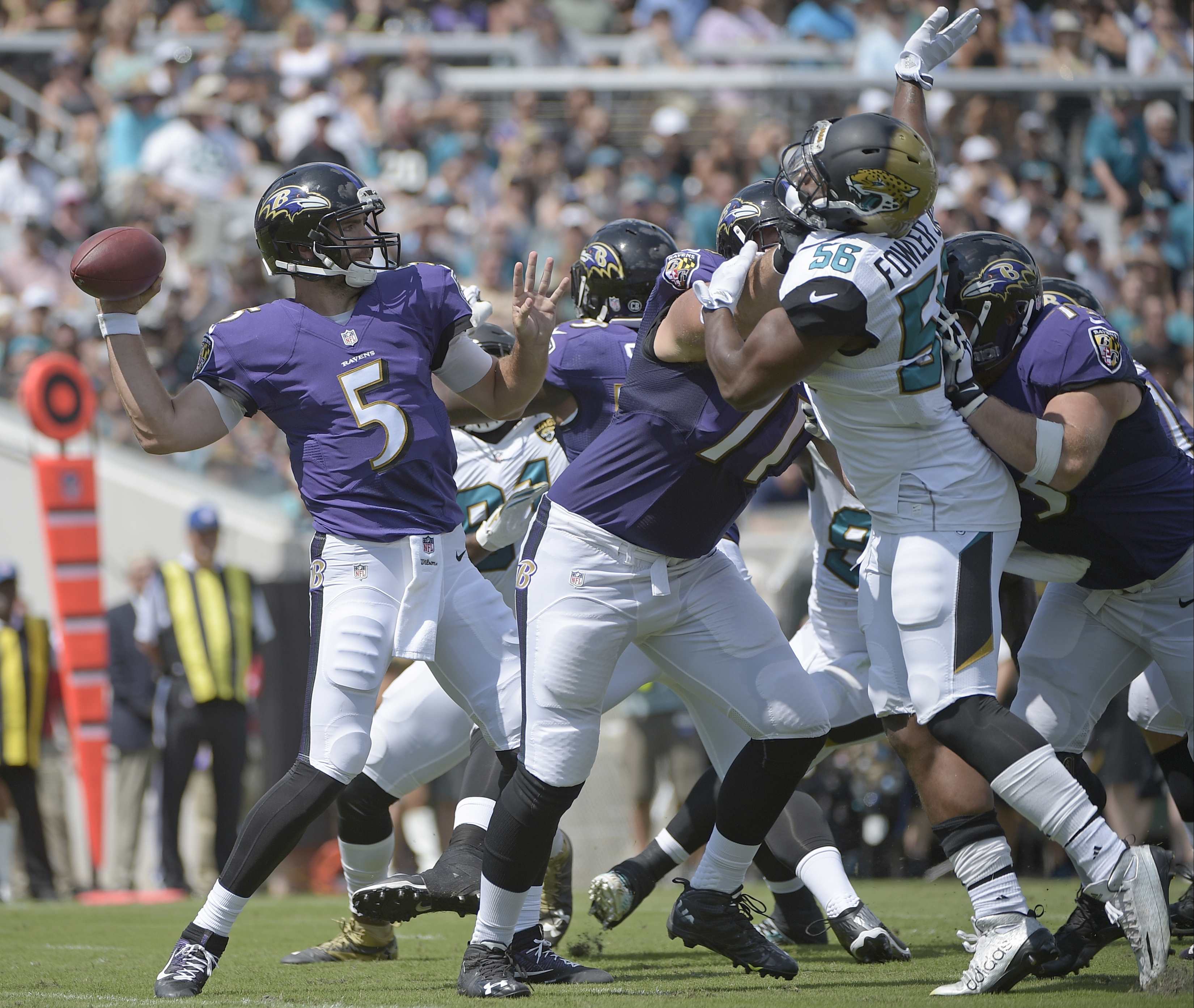 FILE - In this Sept. 25, 2016, file photo, Baltimore Ravens quarterback Joe Flacco (5) throws a pass as he is pressured by Jacksonville Jaguars defensive end Dante Fowler (56) during the first half of an NFL football game in Jacksonville, Fla. On Sunday,