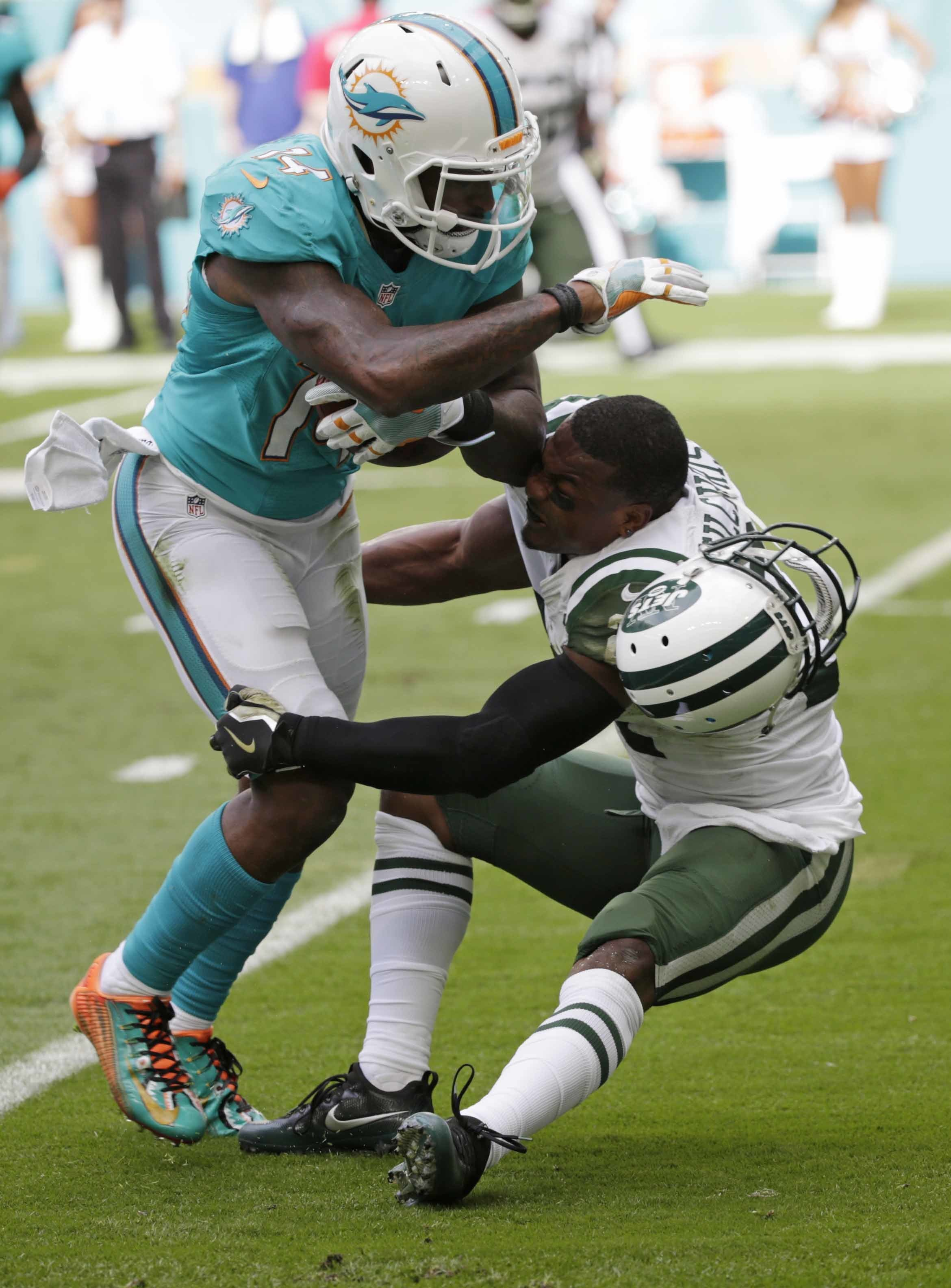 Miami Dolphins wide receiver Jarvis Landry (14) runs the ball as New York Jets free safety Marcus Gilchrist (21), attempts to make the tackle, during the first half of an NFL football game, Sunday, Nov. 6, 2016, in Miami Gardens, Fla. (AP Photo/Wilfredo L