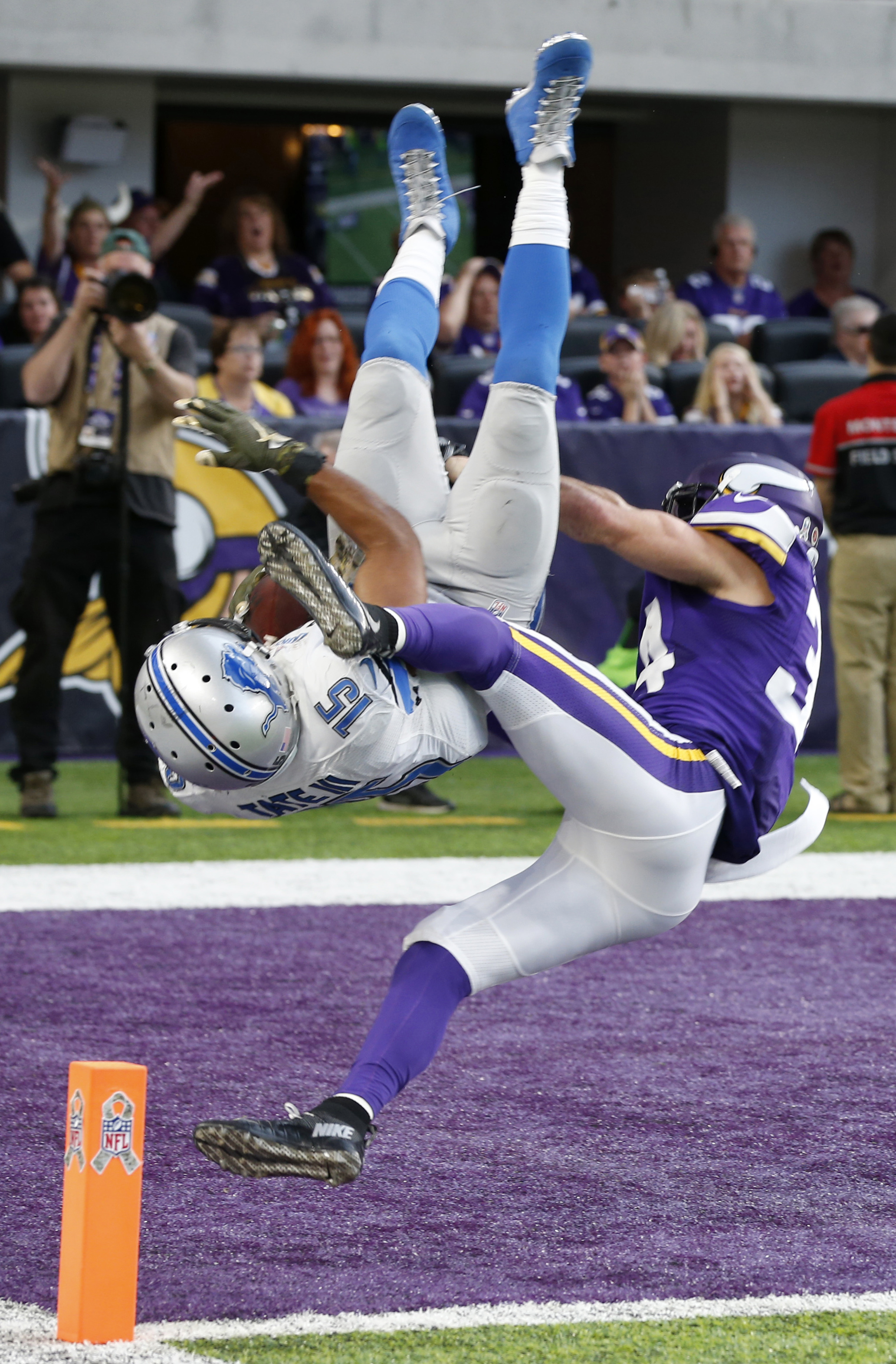 Detroit Lions wide receiver Golden Tate (15) flips into the end zone in front of Minnesota Vikings strong safety Andrew Sendejo, right, after catching a 28-yard touchdown pass during overtime in an NFL football game, Sunday, Nov. 6, 2016, in Minneapolis.