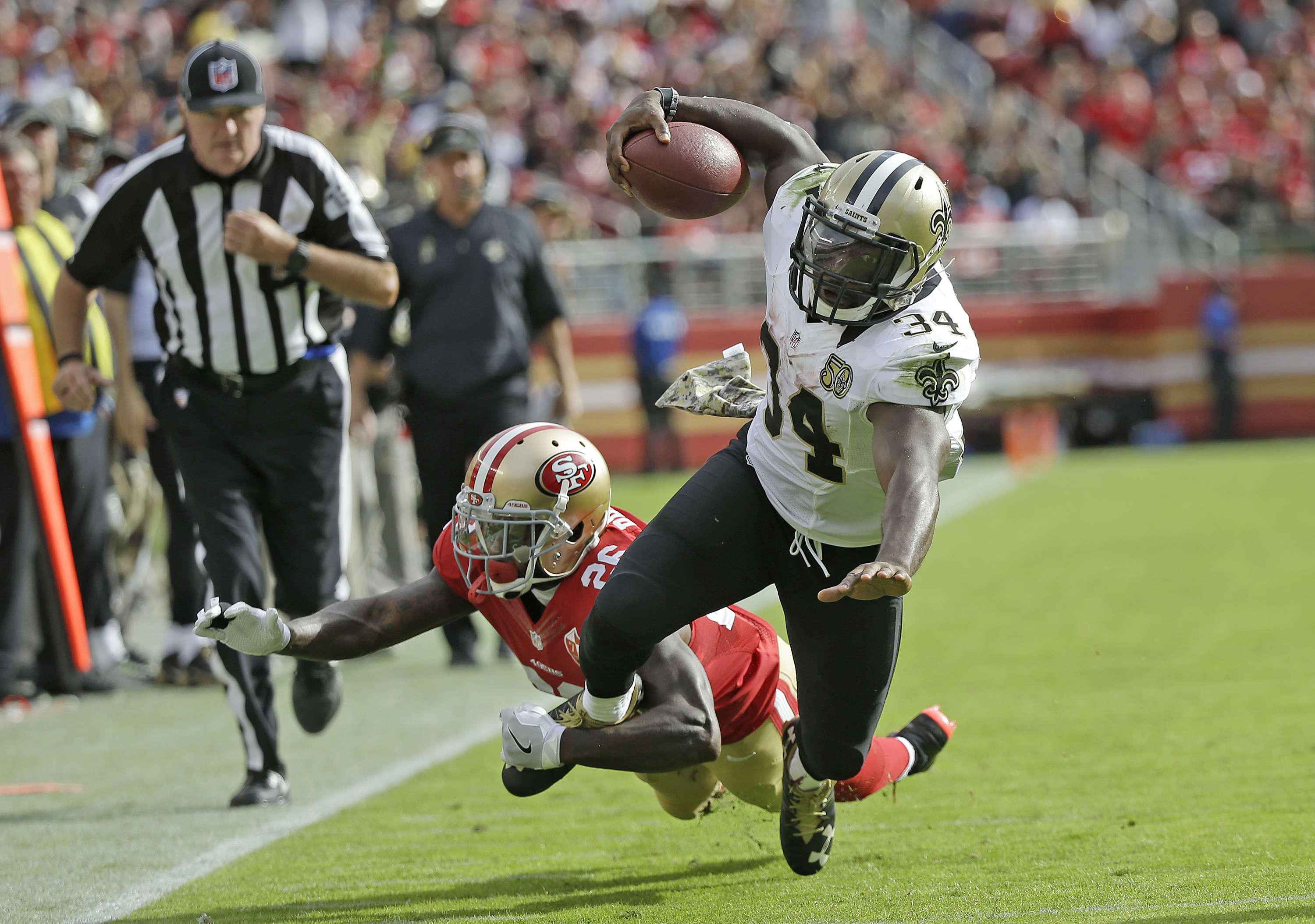 New Orleans Saints running back Tim Hightower goes tumbling with ball while being stopped by San Francisco 49ers cornerback Tramaine Brock, left, during the first half of an NFL football game Sunday, Nov. 6, 2016, in Santa Clara, Calif. (AP Photo/Tony Ave