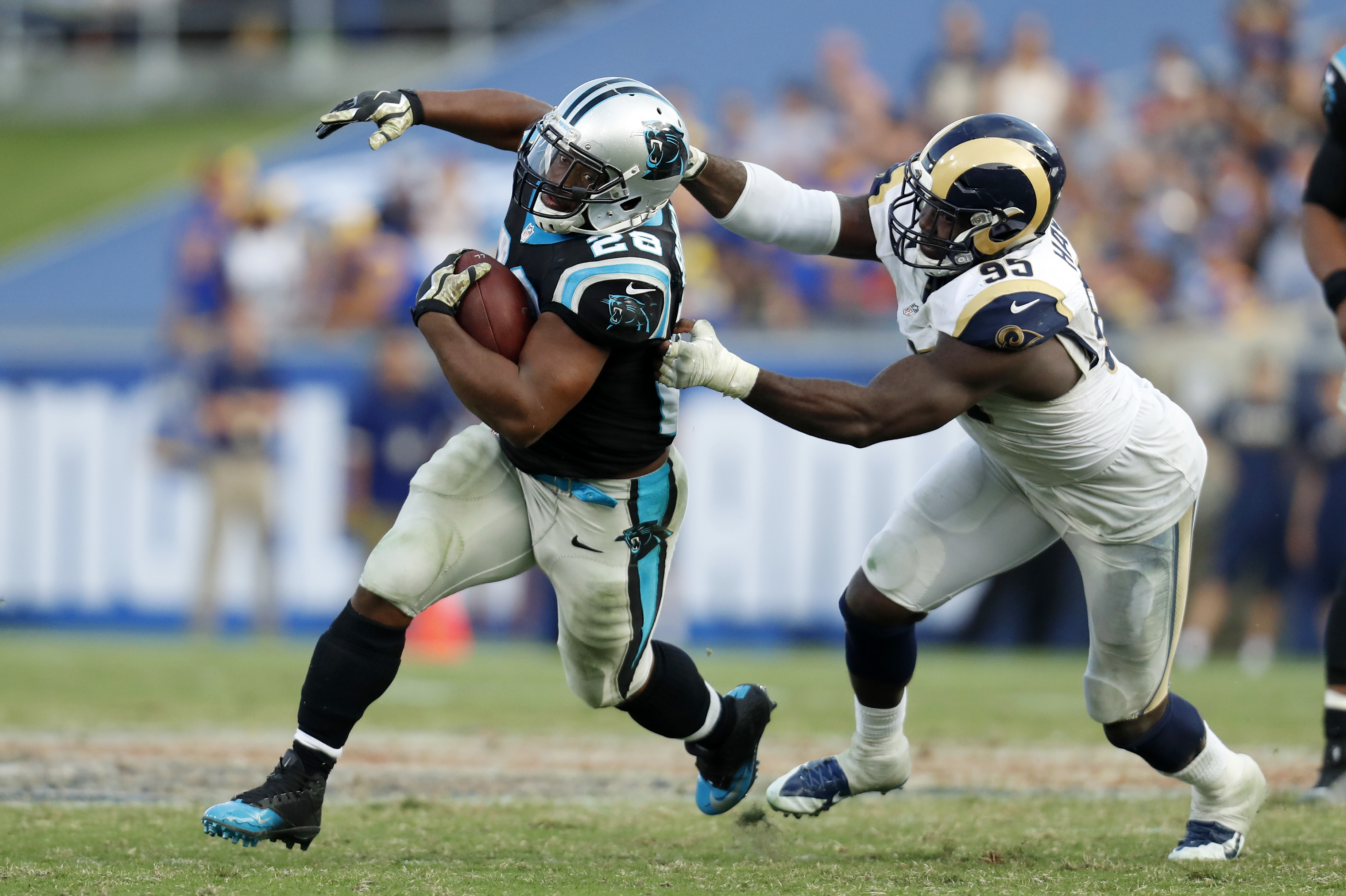 Carolina Panthers running back Jonathan Stewart, left, is grabbed by Los Angeles Rams defensive end William Hayes as he runs the ball during the second half of an NFL football game, Sunday, Nov. 6, 2016, in Los Angeles. (AP Photo/Ryan Kang)