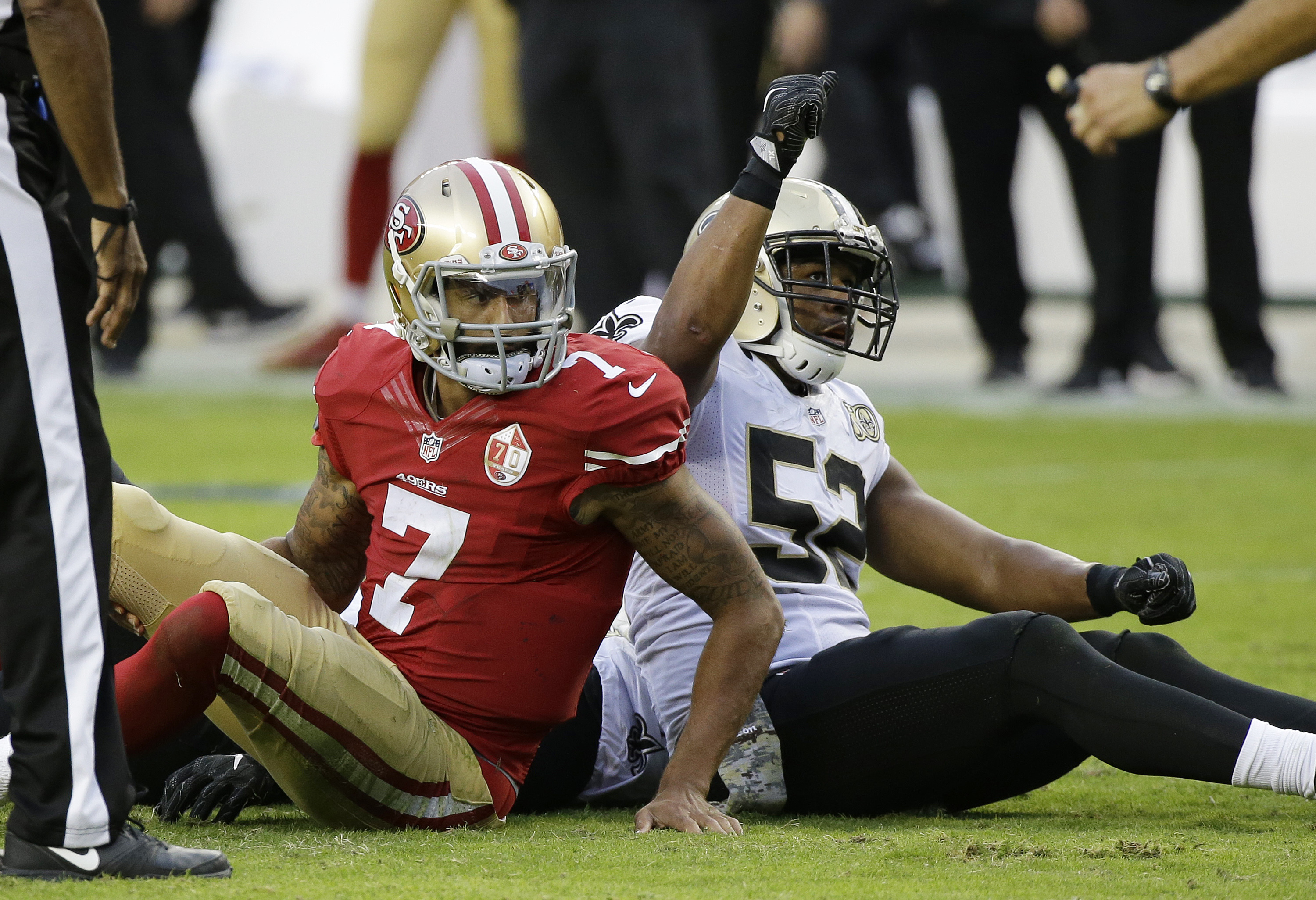 San Francisco 49ers quarterback Colin Kaepernick, left, sits on the field after fumbling the ball as New Orleans Saints outside linebacker Craig Robertson reacts during the second half of an NFL football game Sunday, Nov. 6, 2016, in Santa Clara, Calif. (