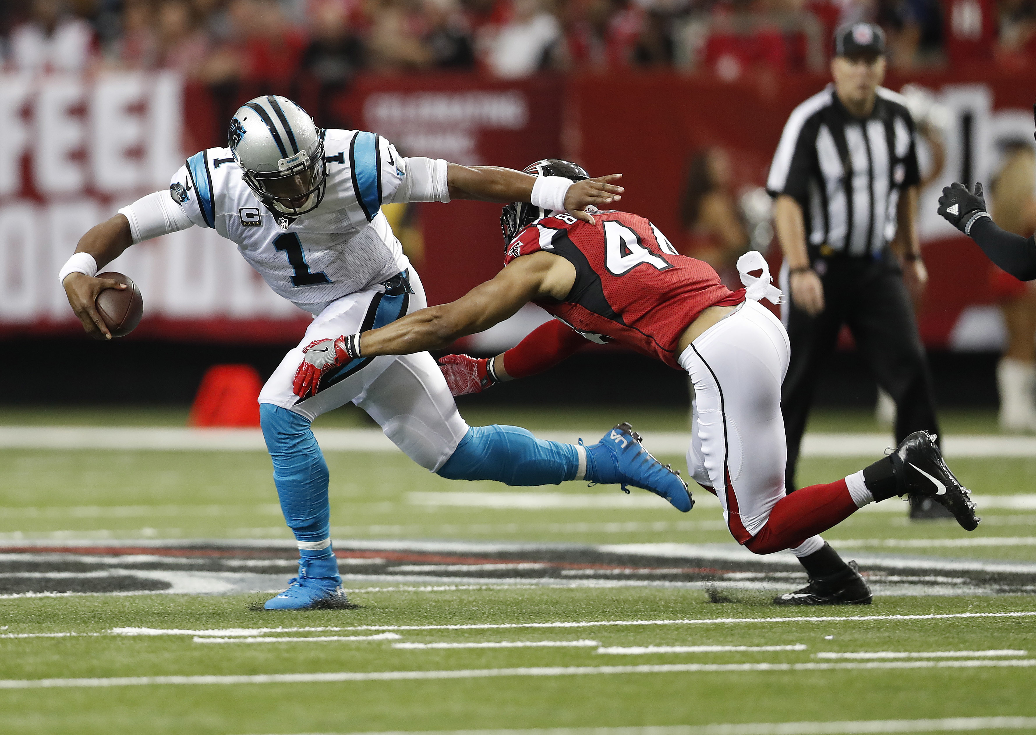 FILE - In this Oct. 2, 2016, file photo, Carolina Panthers quarterback Cam Newton (1) runs out of the pocket against Atlanta Falcons outside linebacker Vic Beasley (44) during the first half of an NFL football game, Sunday, Oct. 2, 2016, in Atlanta. Beasl