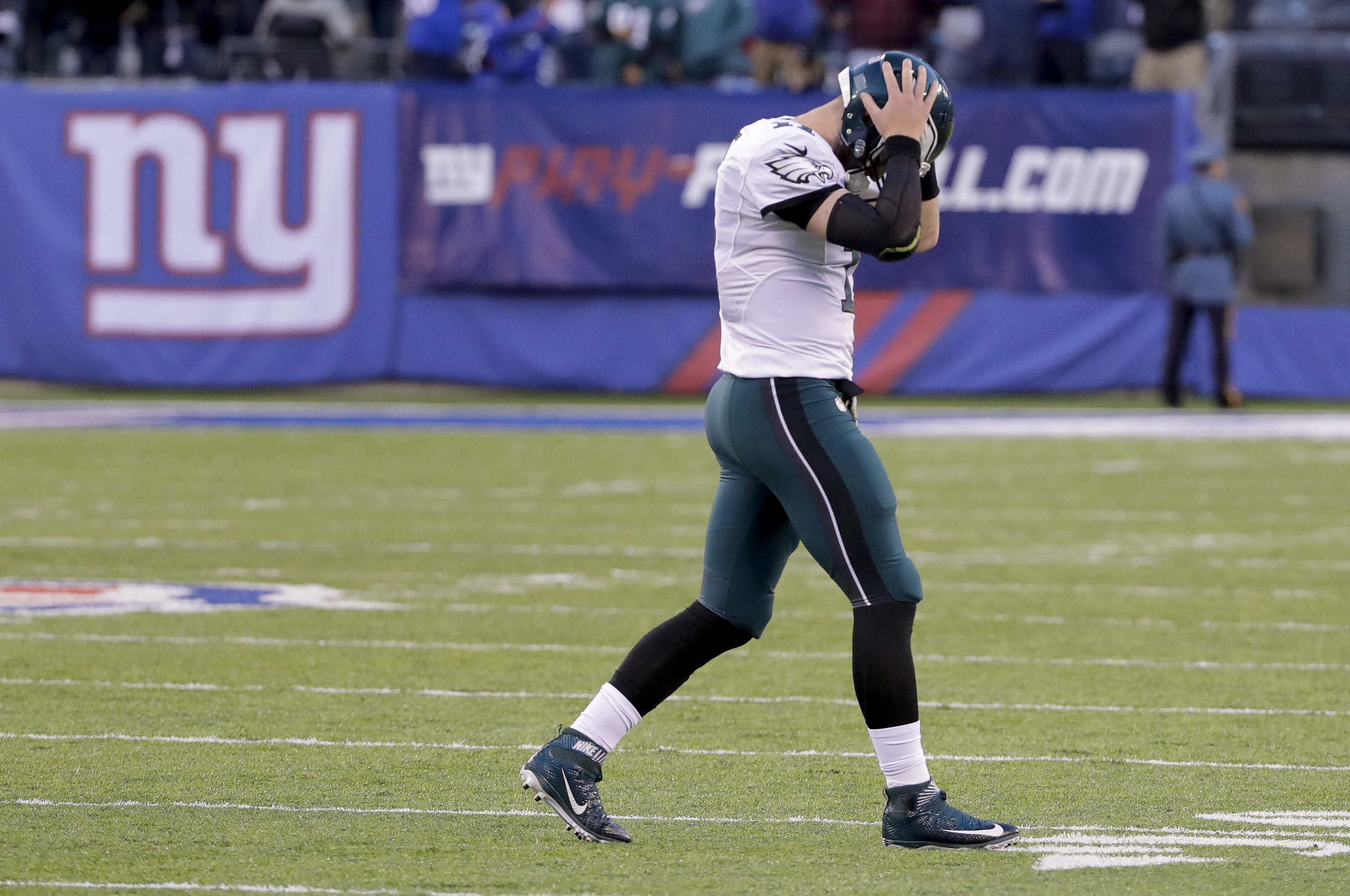 FILE - In this Nov. 6, 2015, file photo, Philadelphia Eagles quarterback Carson Wentz (11) walks off the field after failing to convert on 4th down and 10 against the New York Giants during the fourth quarter of an NFL football game,  in East Rutherford,