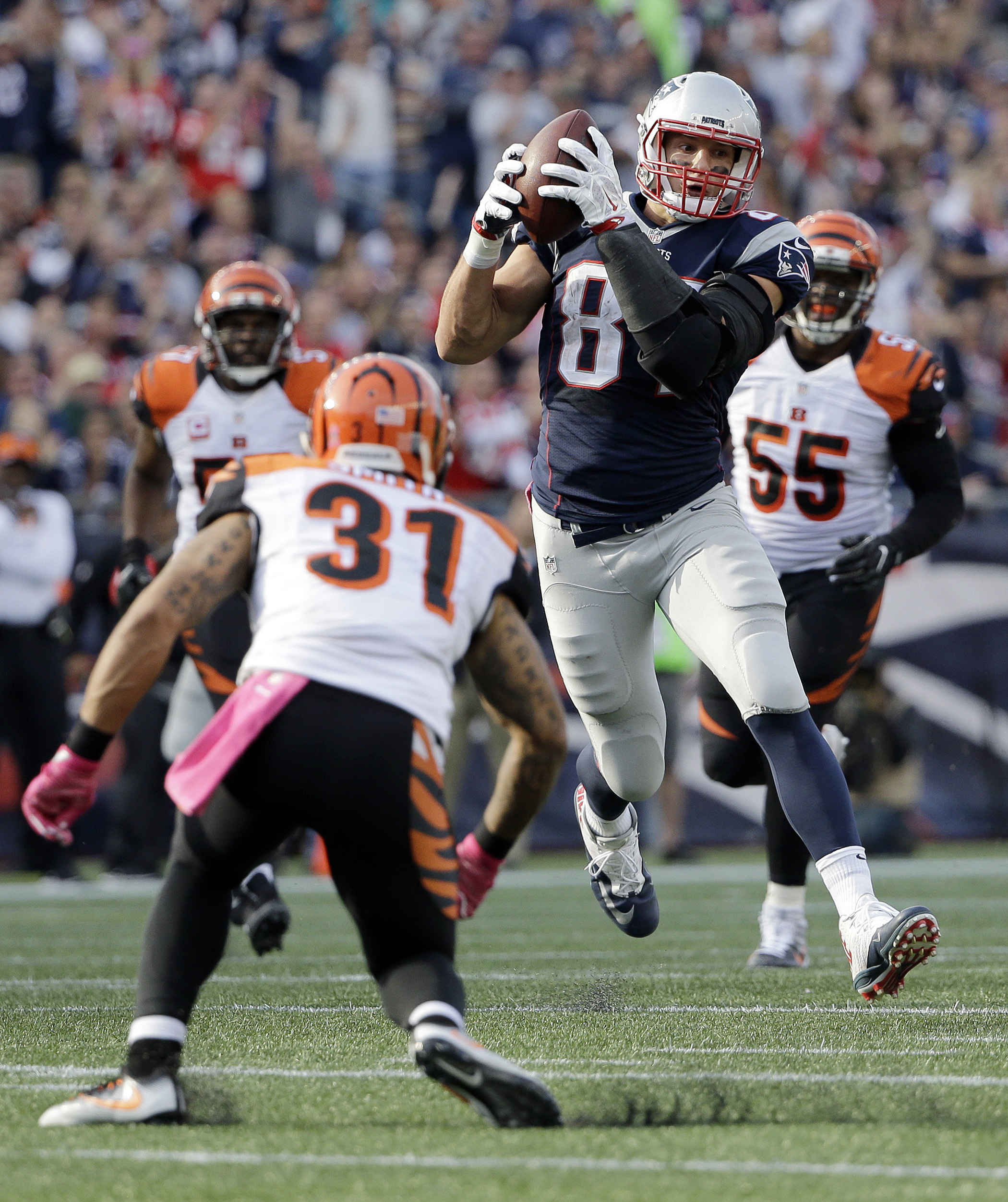 FILE - in this Oct. 16, 2016, file photo, New England Patriots tight end Rob Gronkowski (87) catches a pass between Cincinnati Bengals safety Derron Smith (31) and linebacker Vontaze Burfict (55) during anNFL football game in Foxborough, Mass. The Patriot