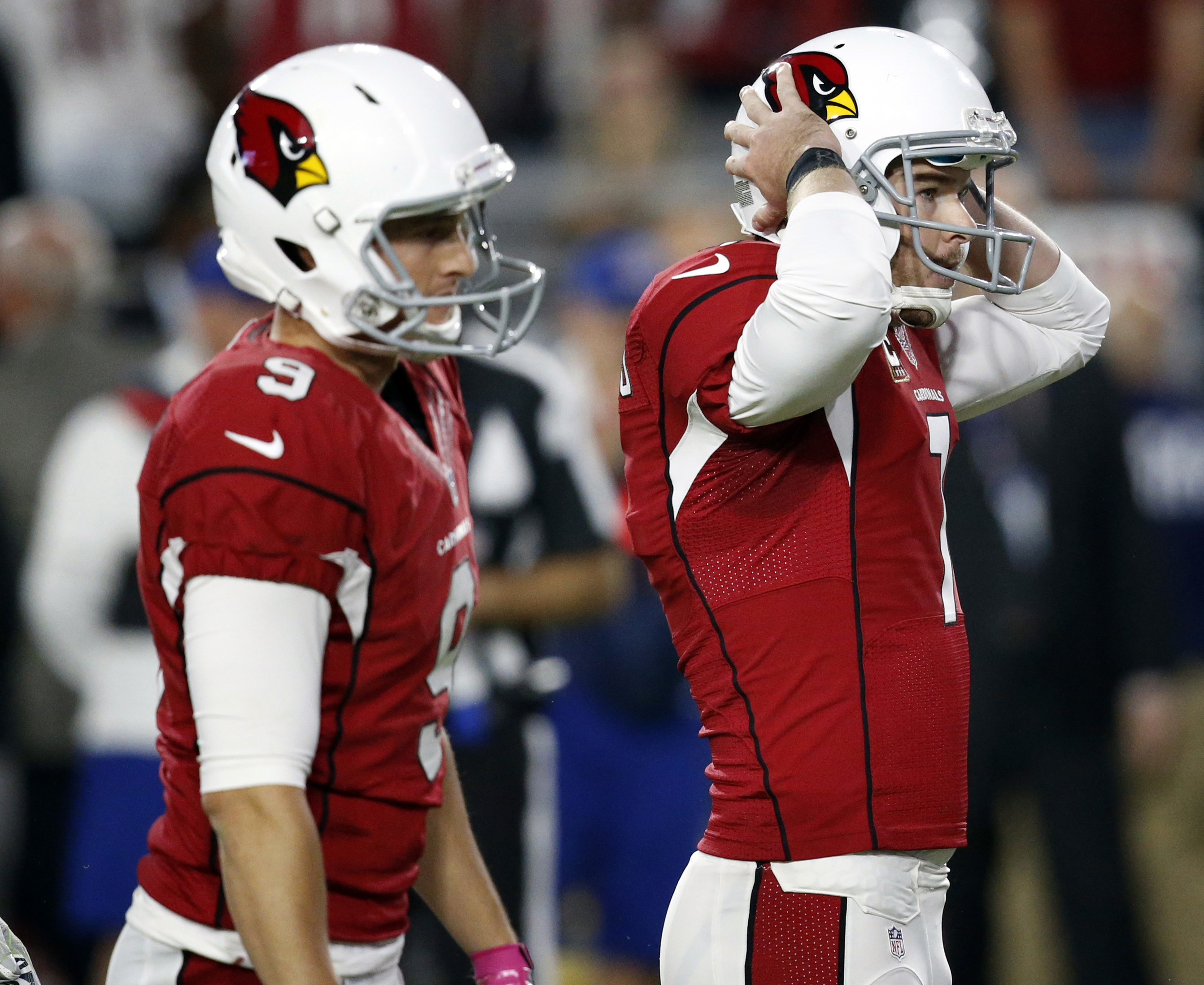 FILE - In this Oct. 23, 2016, file photo, Arizona Cardinals kicker Chandler Catanzaro (7) reacts after missing a field goal as punter Ryan Quigley (9) looks on during overtime of an NFL football game against the Seattle Seahawks in Glendale, Ariz. The gam