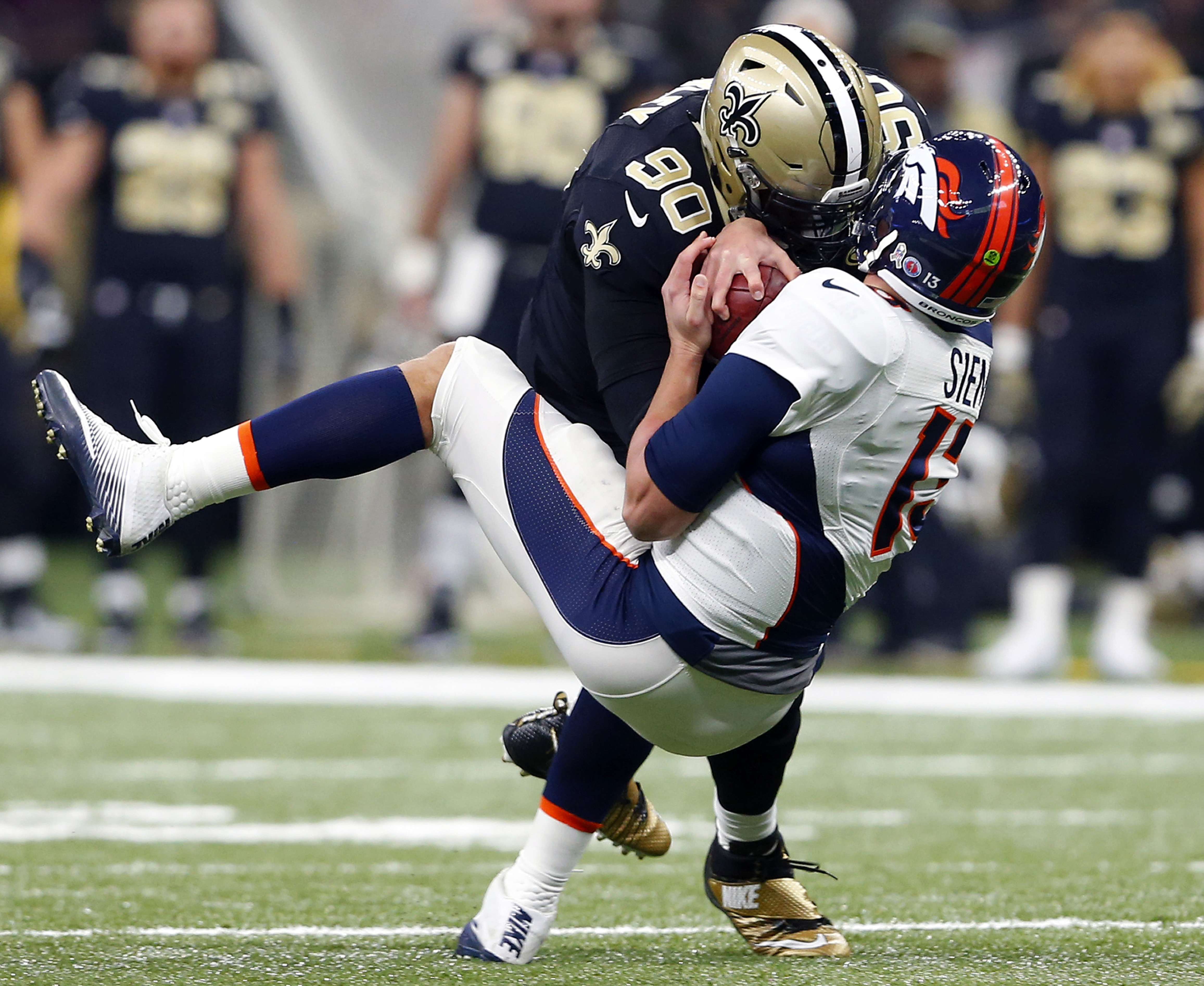 Denver Broncos quarterback Trevor Siemian (13) is sacked by New Orleans Saints defensive tackle Nick Fairley (90) in the first half of an NFL football game in New Orleans, Sunday, Nov. 13, 2016. (AP Photo/Butch Dill)