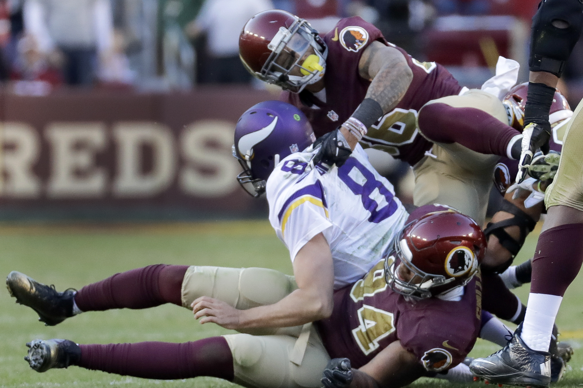 Minnesota Vikings quarterback Sam Bradford (8) is sacked by Washington Redskins linebacker Preston Smith (94) and safety Su'a Cravens (36) during the second half of an NFL football game in Landover, Md., Sunday, Nov. 13, 2016. Washington defeated Minnesot