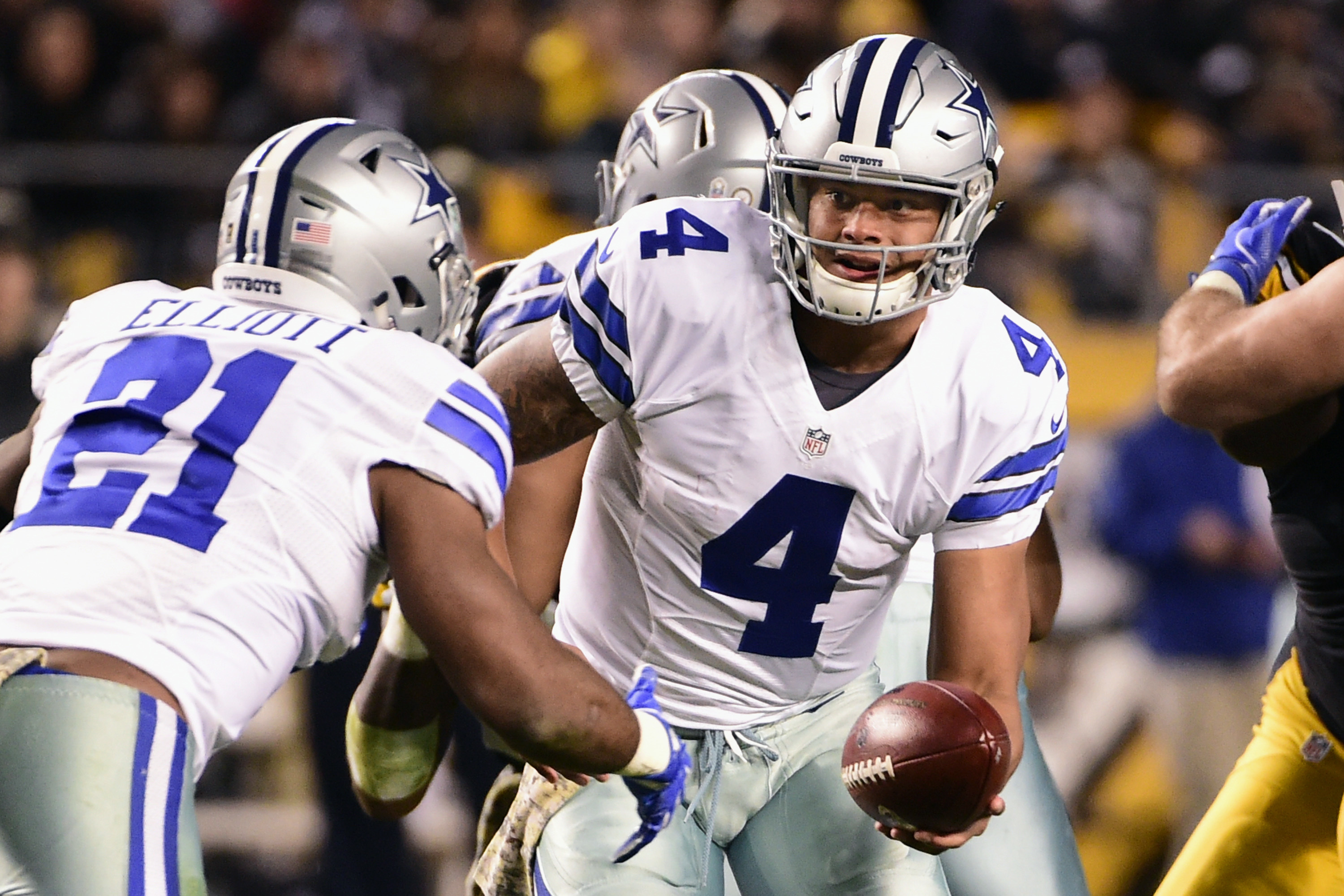 Dallas Cowboys quarterback Dak Prescott (4) hands off the Ezekiel Elliott (21) during the second half of an NFL football game against the Pittsburgh Steelers in Pittsburgh, Sunday, Nov. 13, 2016. (AP Photo/Fred Vuich)