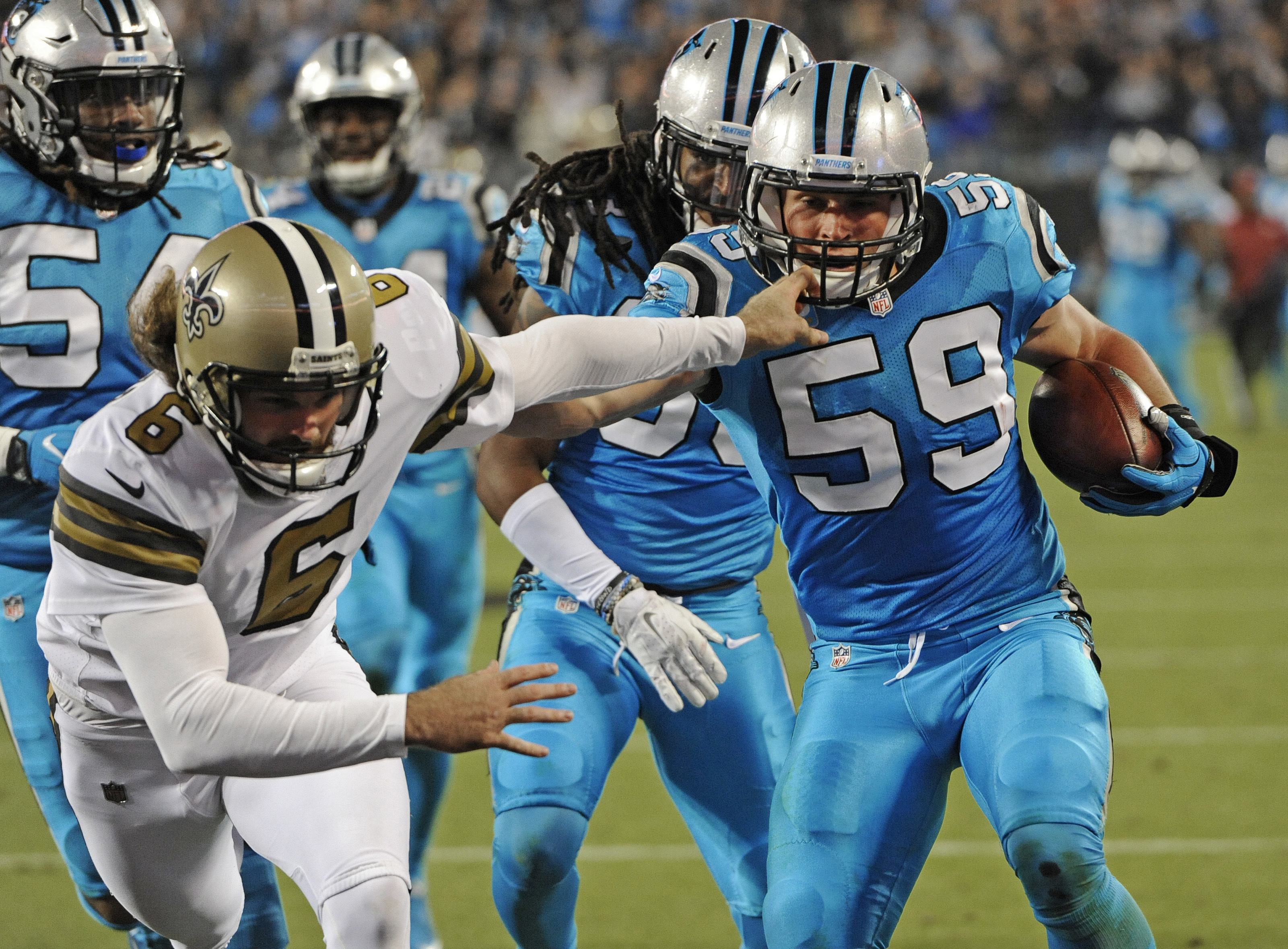 Carolina Panthers' Luke Kuechly (59) runs past New Orleans Saints' Thomas Morstead (6) as he returns a blocked field goal attempt in the first half of an NFL football game in Charlotte, N.C., Thursday, Nov. 17, 2016. (AP Photo/Mike McCarn)
