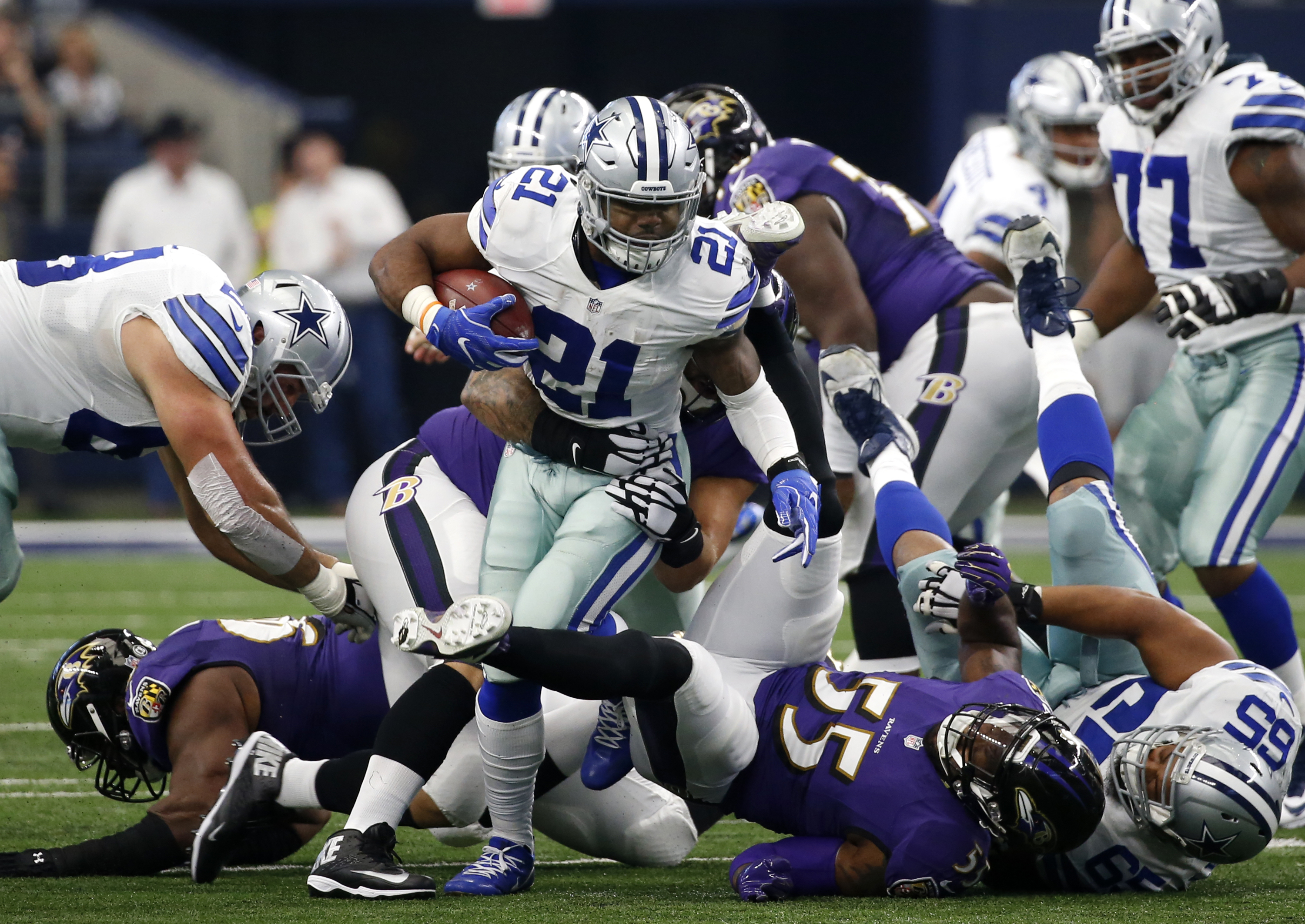 Dallas Cowboys running back Ezekiel Elliott (21) carries the ball as Baltimore Ravens' Terrell Suggs (55) and others attempt the stop in the first half of an NFL football game, Sunday, Nov. 20, 2016, in Arlington, Texas. (AP Photo/Michael Ainsworth)