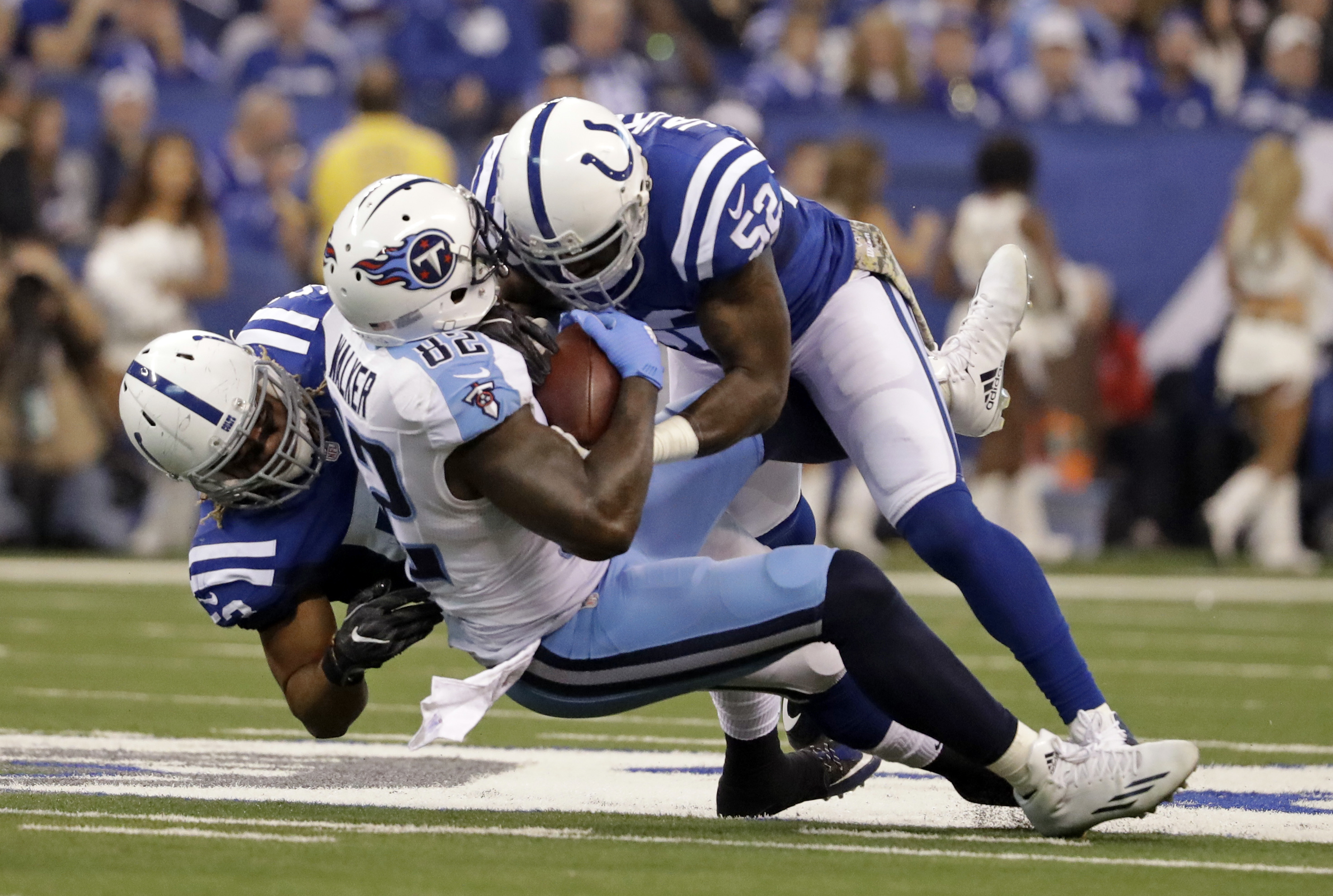 Indianapolis Colts linebacker Edwin Jackson (53) and linebacker D'Qwell Jackson (52) tackles Tennessee Titans tight end Delanie Walker (82) during the first half of an NFL football game in Indianapolis, Sunday, Nov. 20, 2016. (AP Photo/Jeff Roberson)