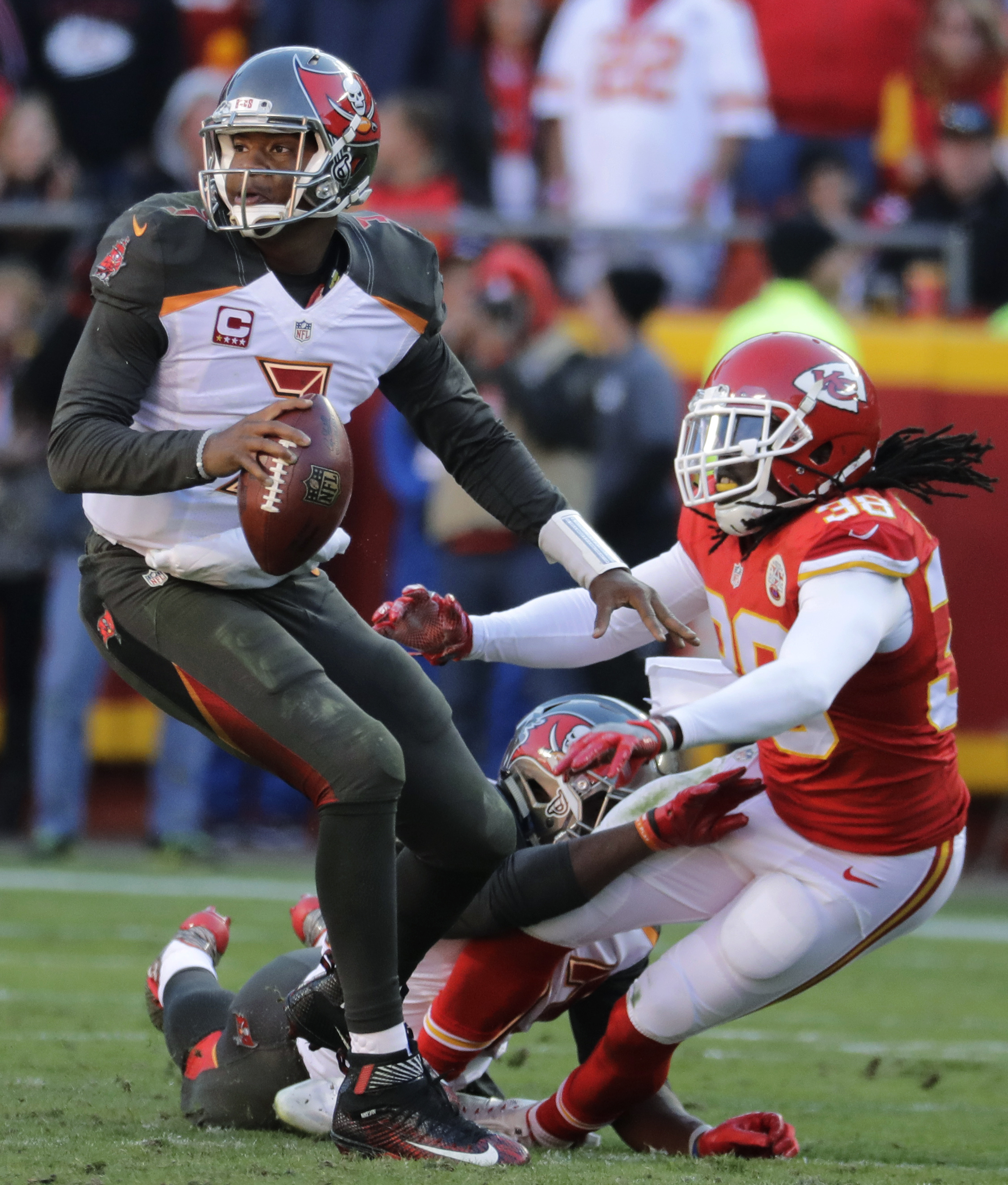 Tampa Bay Buccaneers quarterback Jameis Winston (3) looks for a receiver as Kansas City Chiefs defensive back Ron Parker (38) is tackled by running back Peyton Barber (43) during the second half of an NFL football game in Kansas City, Mo., Sunday, Nov. 20