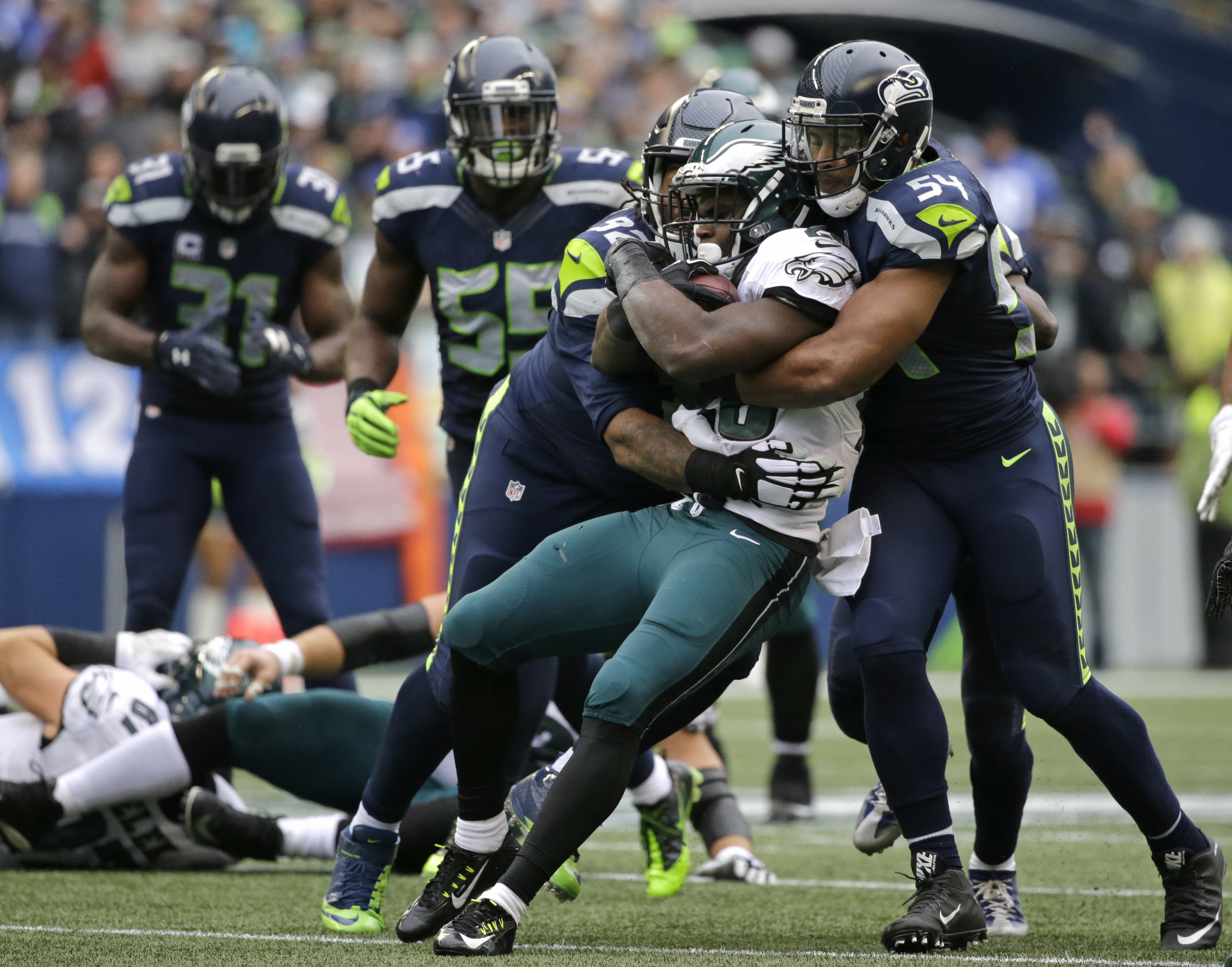 Philadelphia Eagles running back Wendell Smallwood is wrapped up by Seattle Seahawks middle linebacker Bobby Wagner, right, and defensive tackle John Jenkins in the first half of an NFL football game, Sunday, Nov. 20, 2016, in Seattle. (AP Photo/John Fros
