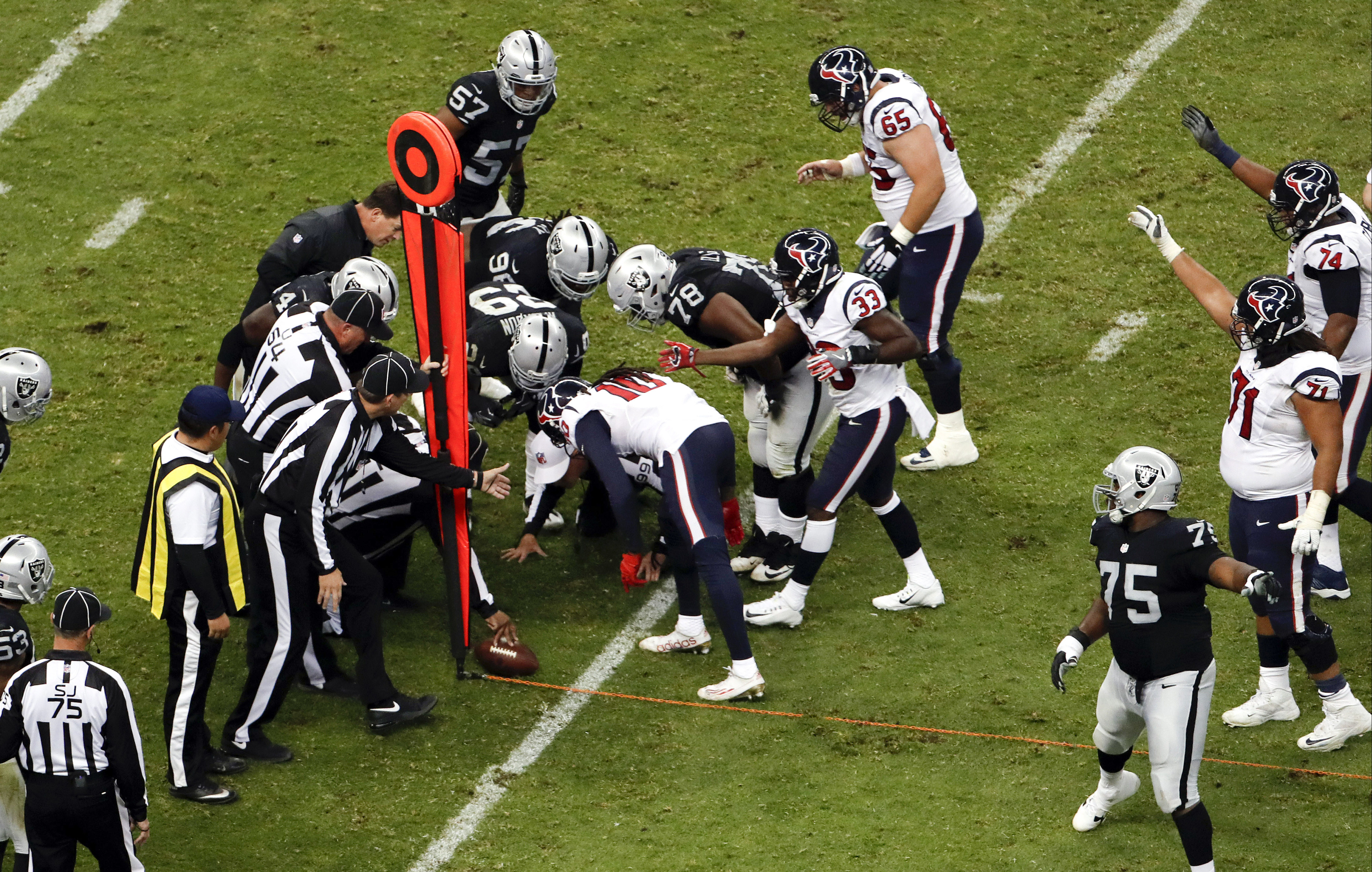 Referees measure as the Houston Texans fall short of getting a first down during the second half of an NFL football game against the Oakland Raiders Monday, Nov. 21, 2016, in Mexico City. (AP Photo/Dario Lopez-Mills)