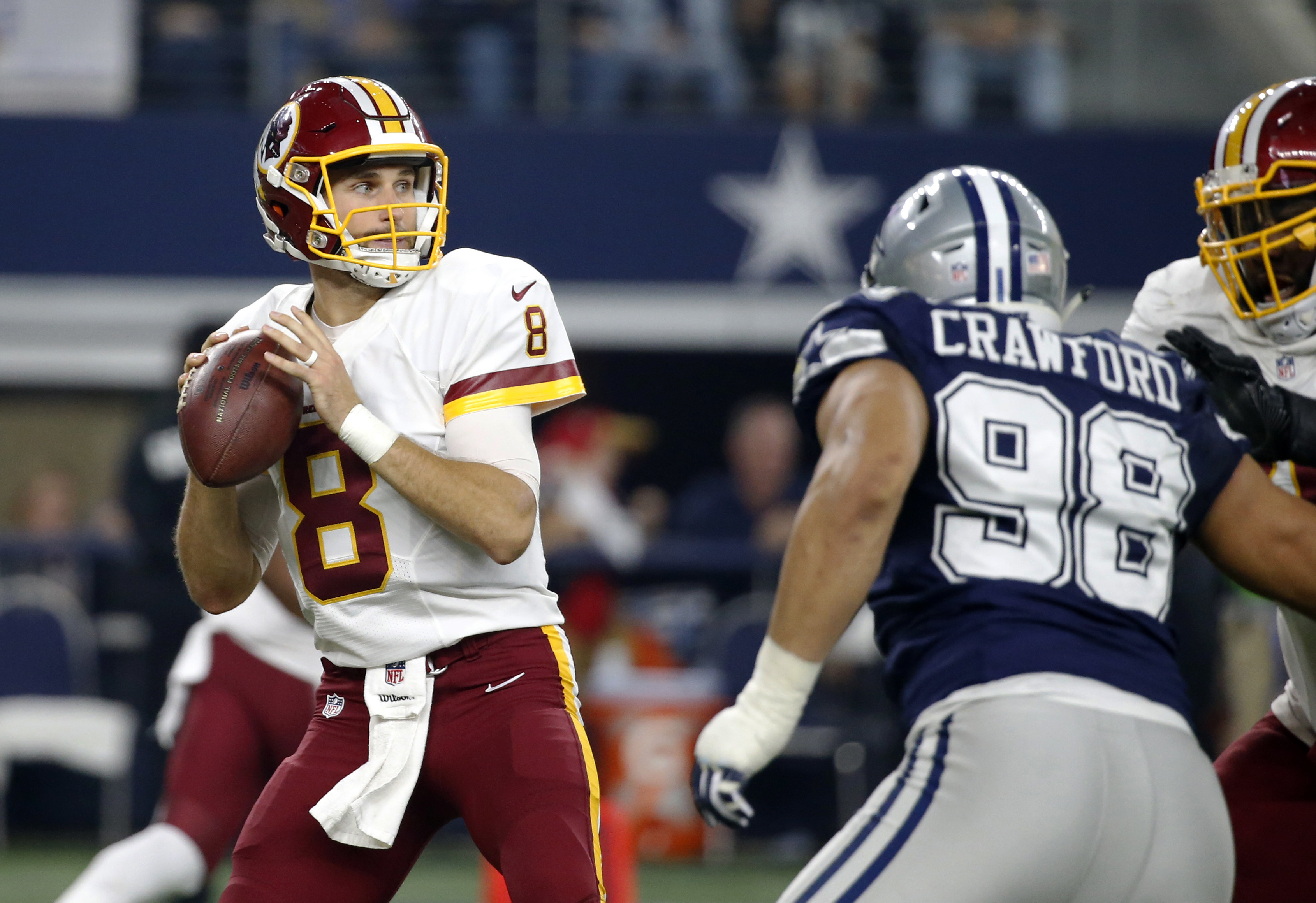 Washington Redskins quarterback Kirk Cousins (8) prepares to throw a pass under pressure from Dallas Cowboys' Tyrone Crawford (98) during the first half of an NFL football game, Thursday, Nov. 24, 2016, in Arlington, Texas. (AP Photo/Michael Ainsworth)