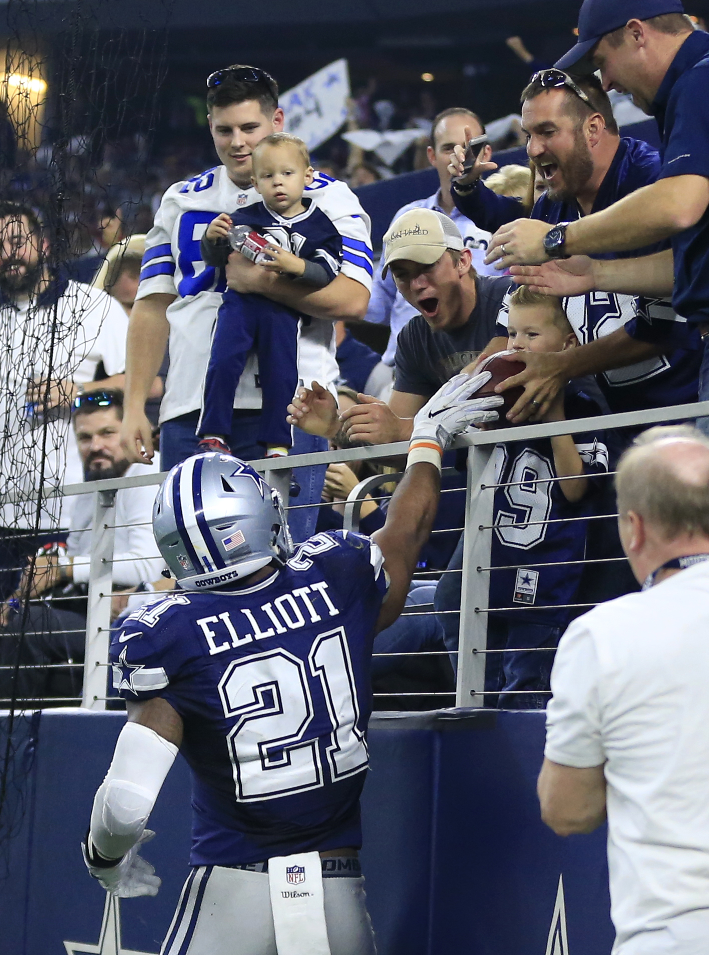 Dallas Cowboys running back Ezekiel Elliott (21) hands the ball to a young child after scoring a touchdown against the Washington Redskins during the second half of an NFL football game, Thursday, Nov. 24, 2016, in Arlington, Texas. (AP Photo/Ron Jenkins)