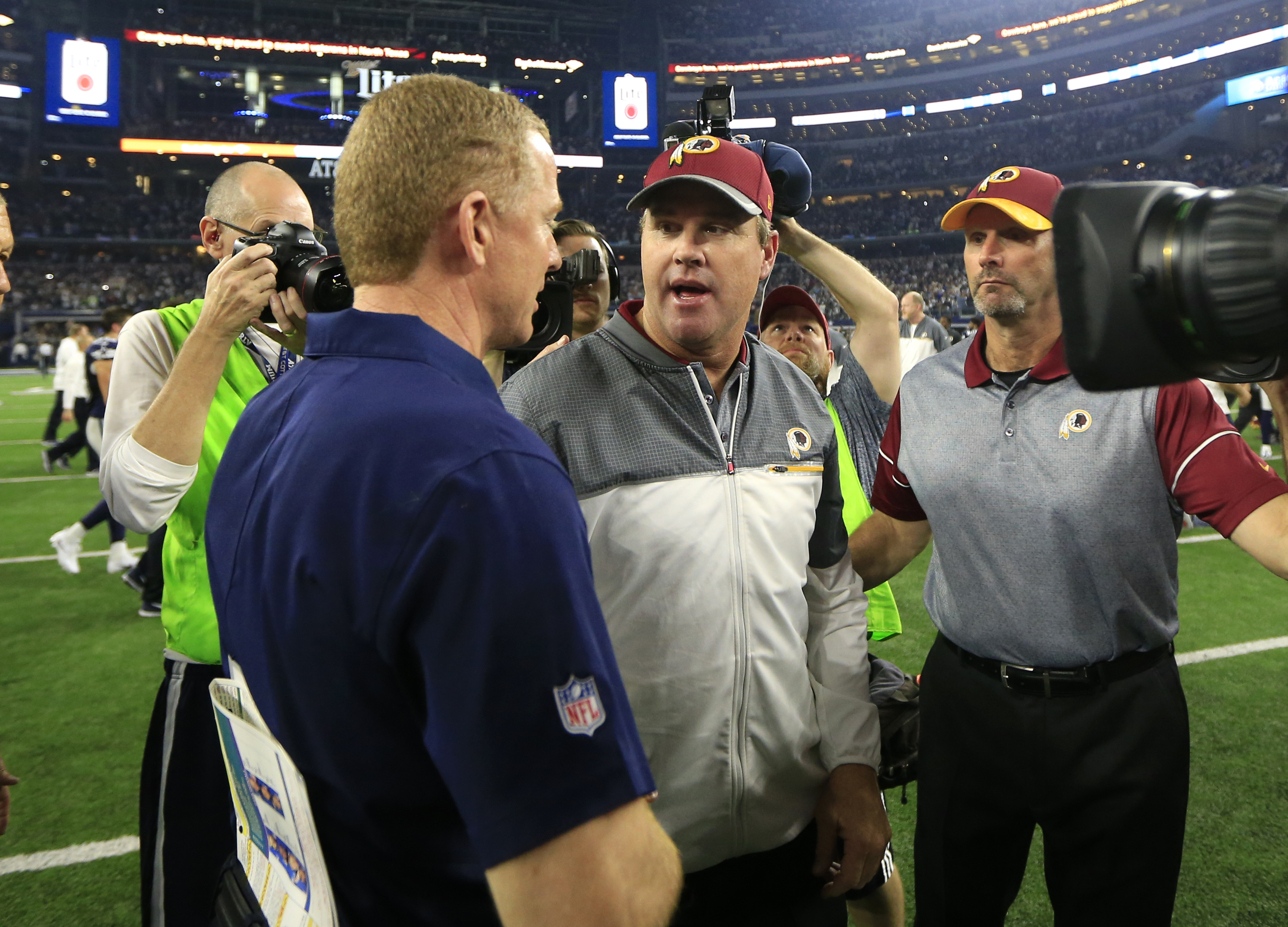 Dallas Cowboys coach Jason Garrett, left, and Washington Redskins coach Jay Gruden, center, greet each other after an NFL football game, Thursday, Nov. 24, 2016, in Arlington, Texas. Dallas won 31-26. (AP Photo/Ron Jenkins)
