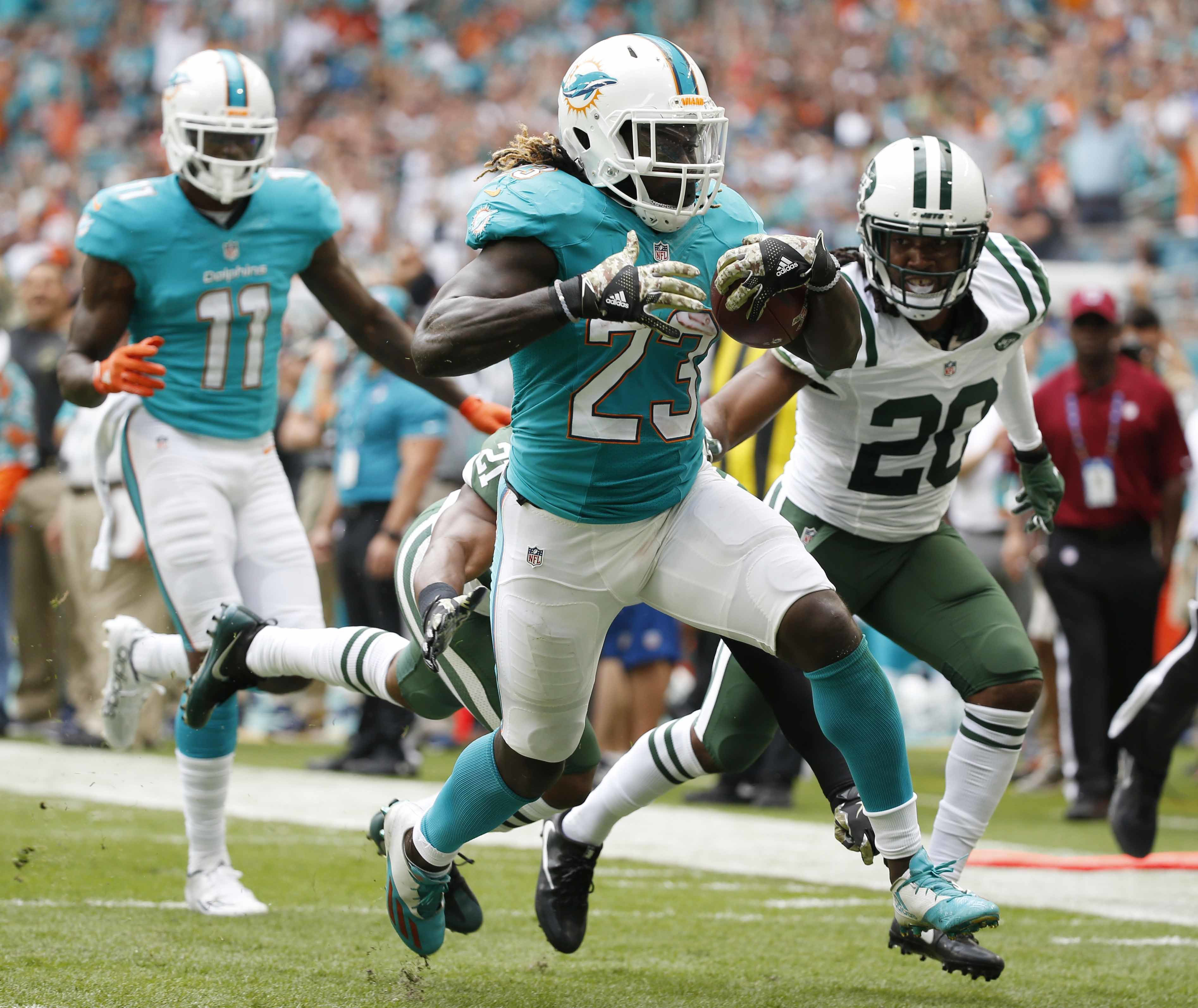 FILE - In a Sunday, Nov. 6, 2016 file photo, Miami Dolphins running back Jay Ajayi (23) runs for a touchdown ahead of New York Jets cornerback Marcus Williams (20), during the first half of an NFL football game, in Miami Gardens, Fla.  No team is a bigger