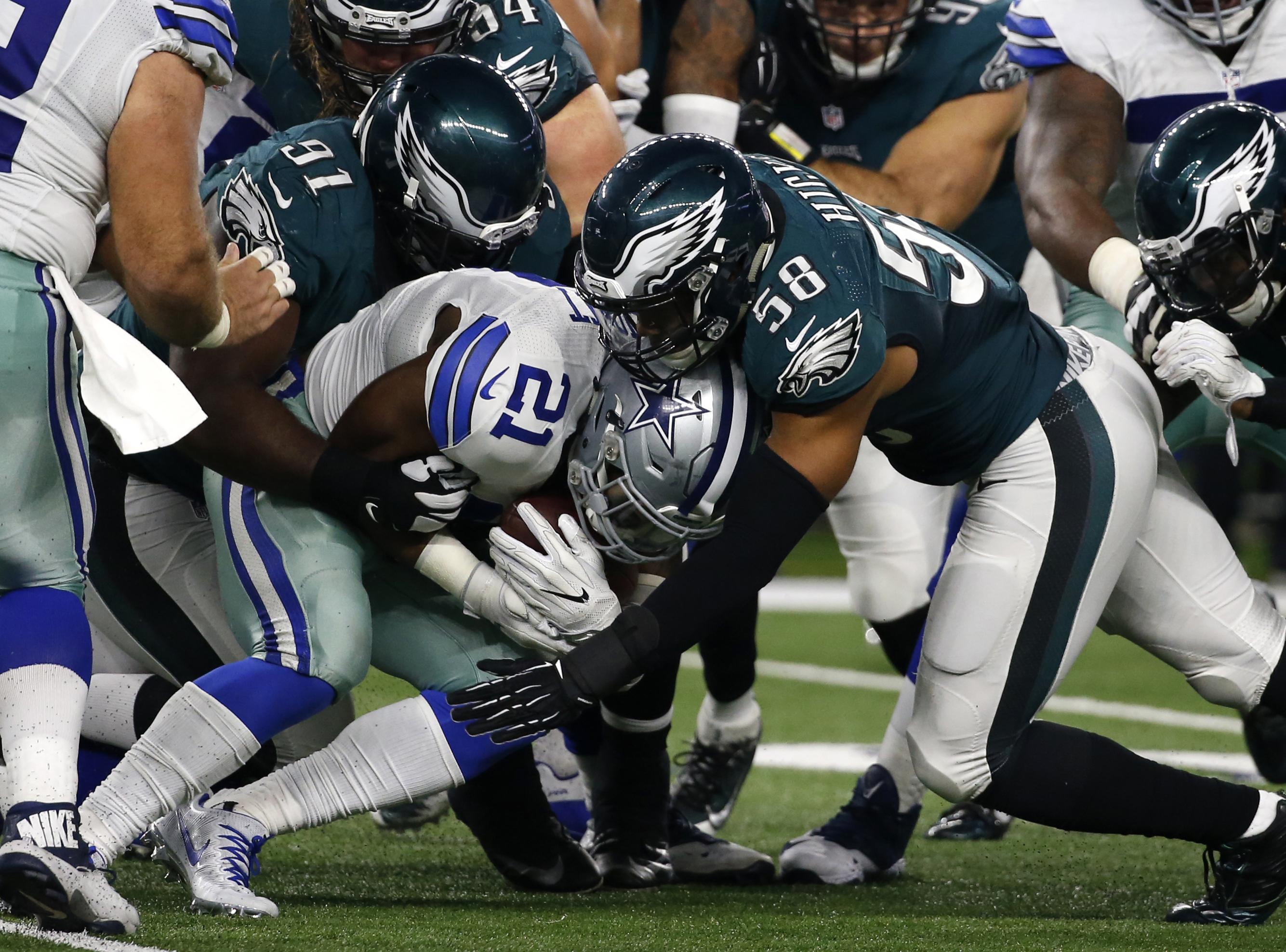 FILE - In a Sunday, Oct. 30, 2016 file photo, Dallas Cowboys running back Ezekiel Elliott (21) is stopped on a run by Philadelphia Eagles defensive tackle Fletcher Cox (91) and middle linebacker Jordan Hicks (58) in the second half of an NFL football game