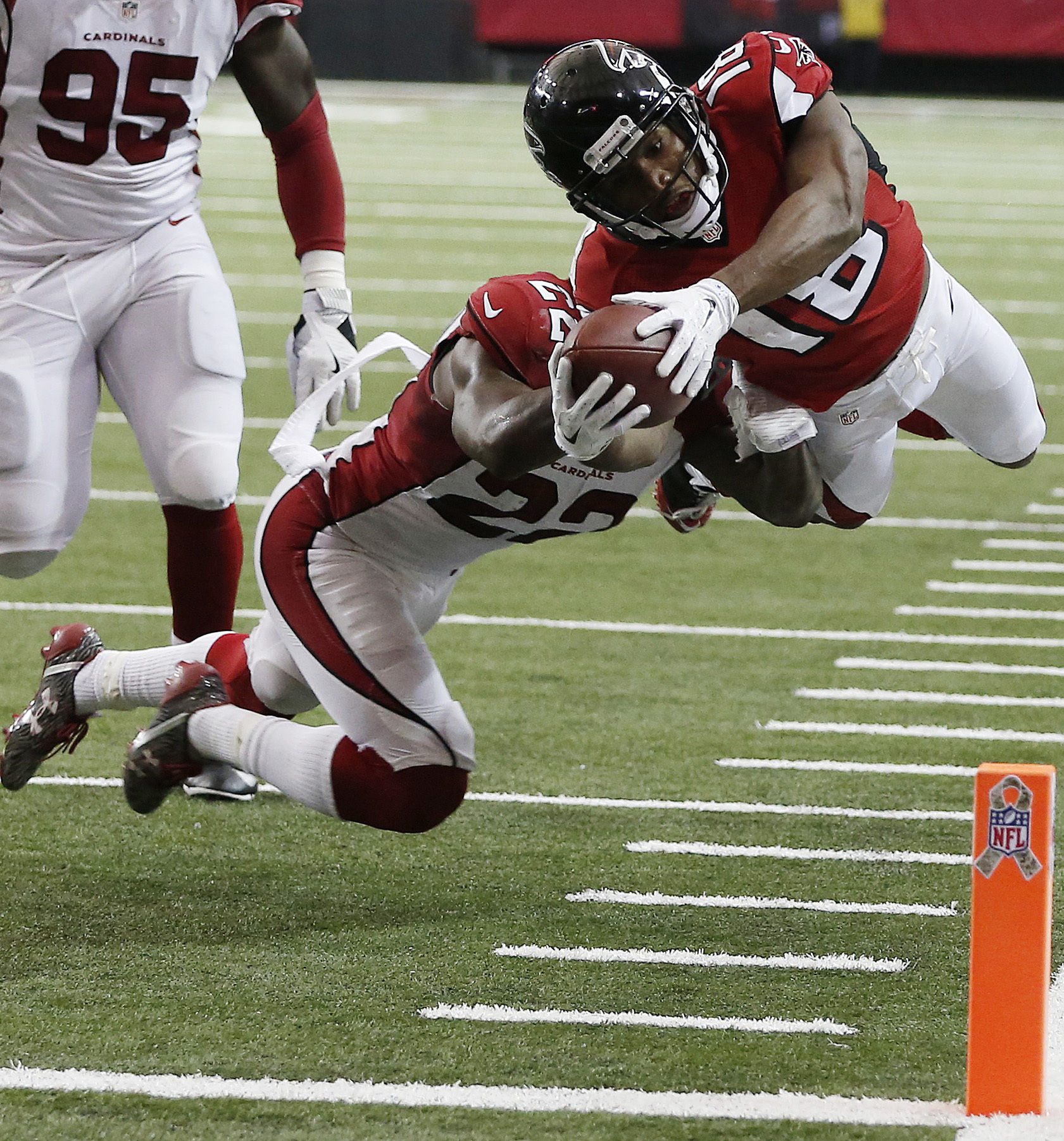 Atlanta Falcons wide receiver Taylor Gabriel (18) leaps into the end zone for a touchdown against Arizona Cardinals strong safety Tony Jefferson (22) during the second of an NFL football game, Sunday, Nov. 27, 2016, in Atlanta. (AP Photo/John Bazemore)
