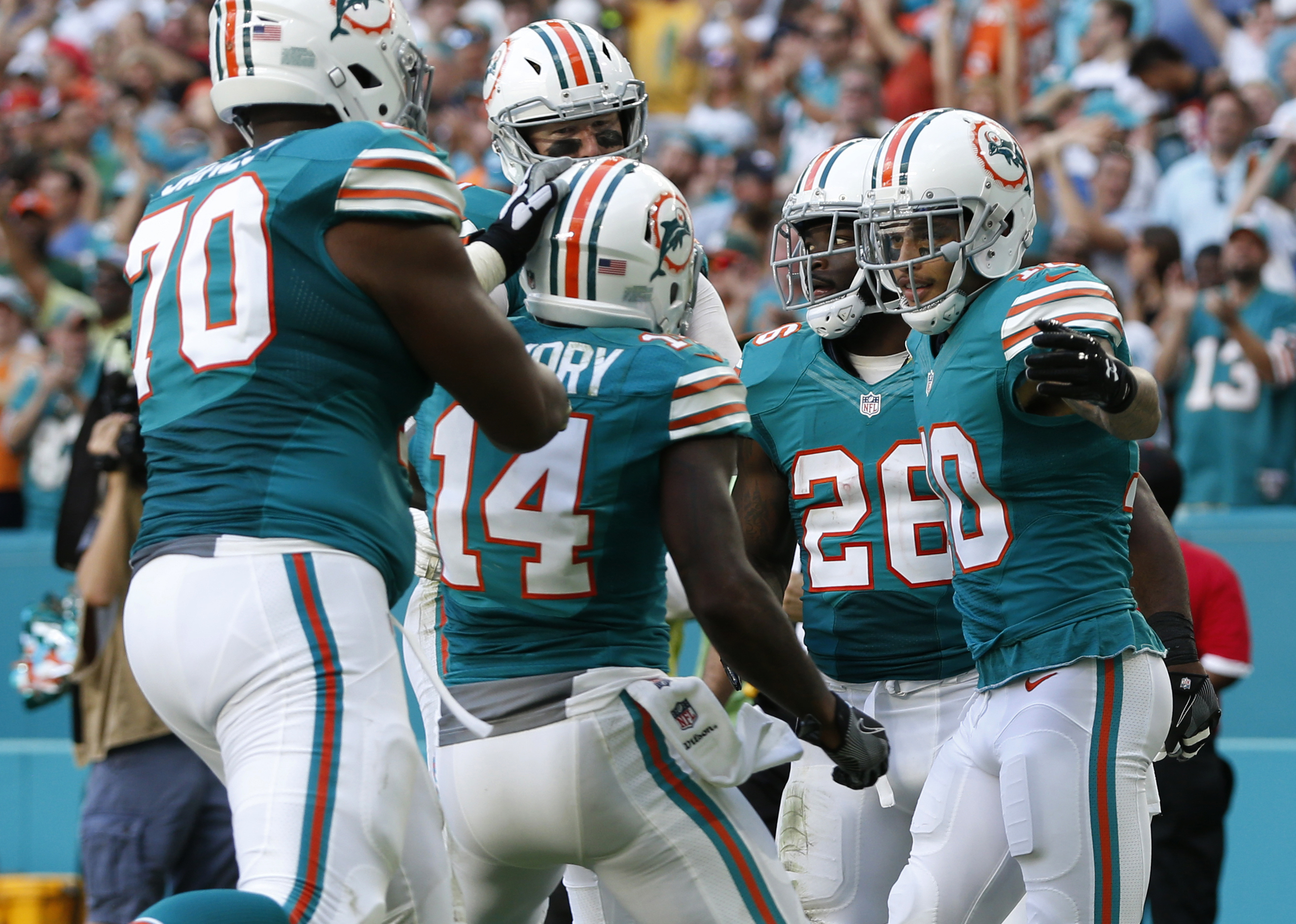 Miami Dolphins tackle Ja'Wuan James (70), and wide receiver Jarvis Landry (14) congratulate wide receiver Kenny Stills (10), after Stills scored a touchdown, during the second half of an NFL football game against the San Francisco 49ers, Sunday, Nov. 27,