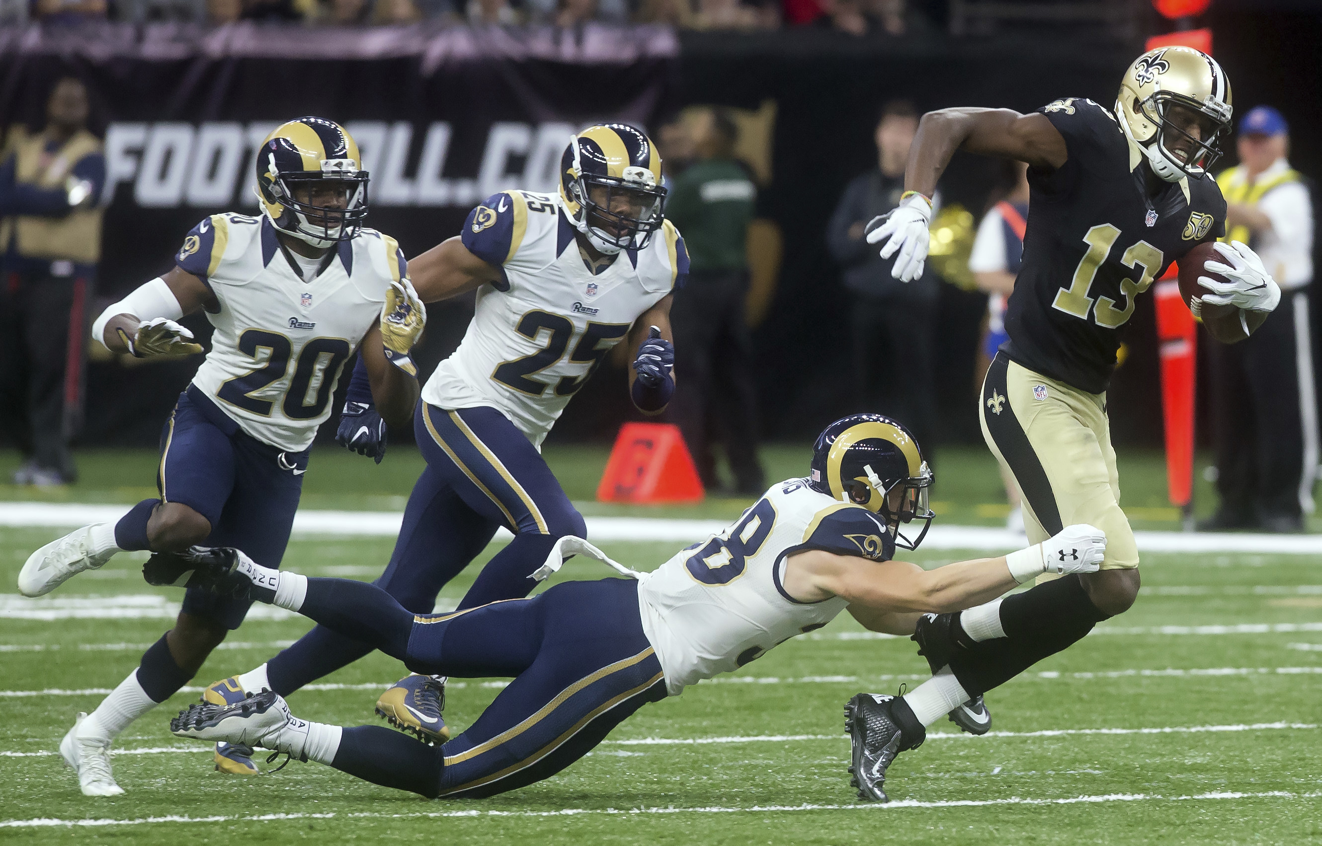 New Orleans Saints wide receiver Michael Thomas stretches to avoid the tackle of Los Angeles Rams' Cody Davis (38) as Rams' LaMarcus Joyner (20) and T.J. McDonald (25) trail the play during an NFL football game in New Orleans, Sunday, Nov. 27, 2016. (Chri