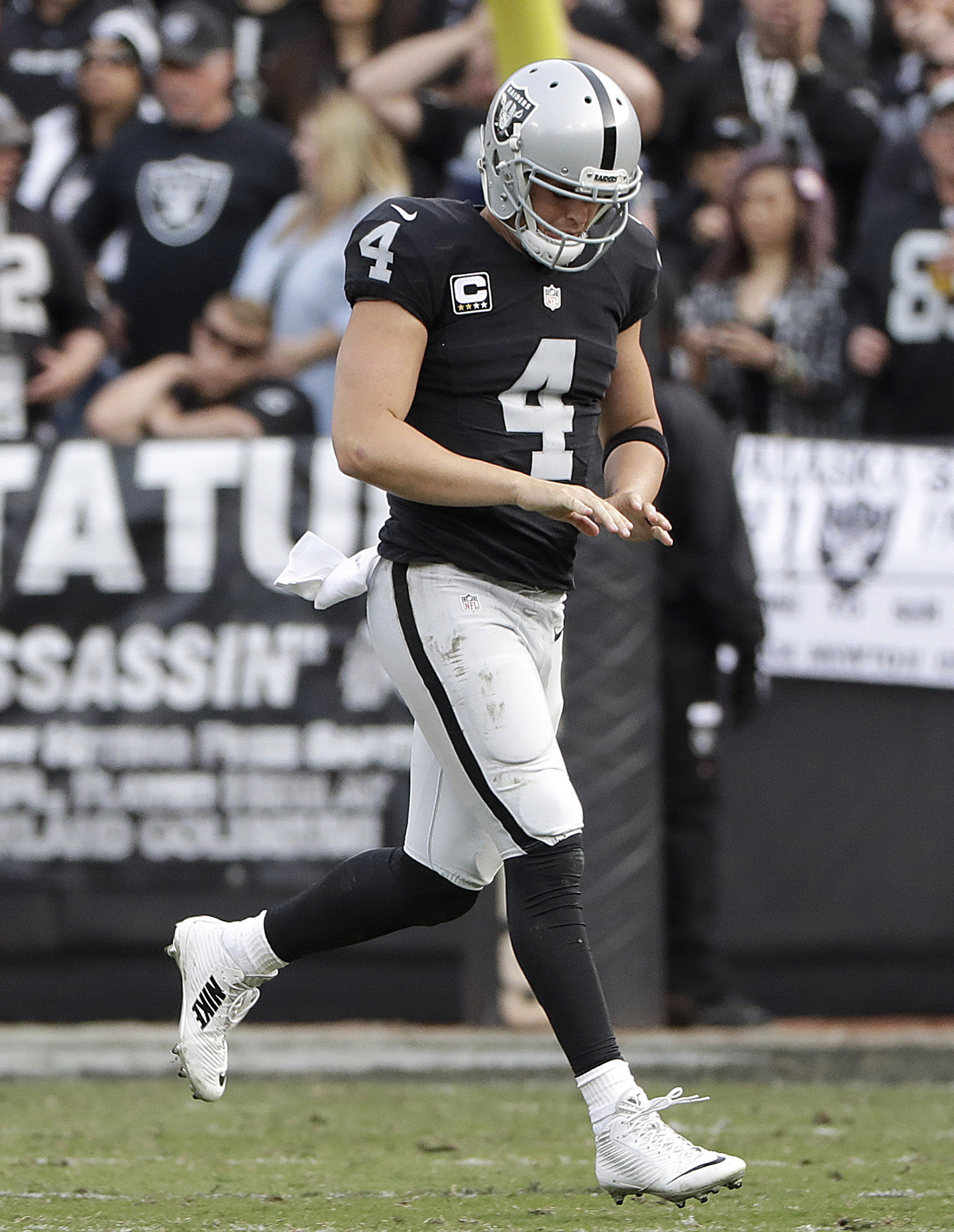 Oakland Raiders quarterback Derek Carr (4) runs off the field after an injury to his hand during the second half of an NFL football game against the Carolina Panthers in Oakland, Calif., Sunday, Nov. 27, 2016. (AP Photo/Marcio Jose Sanchez)
