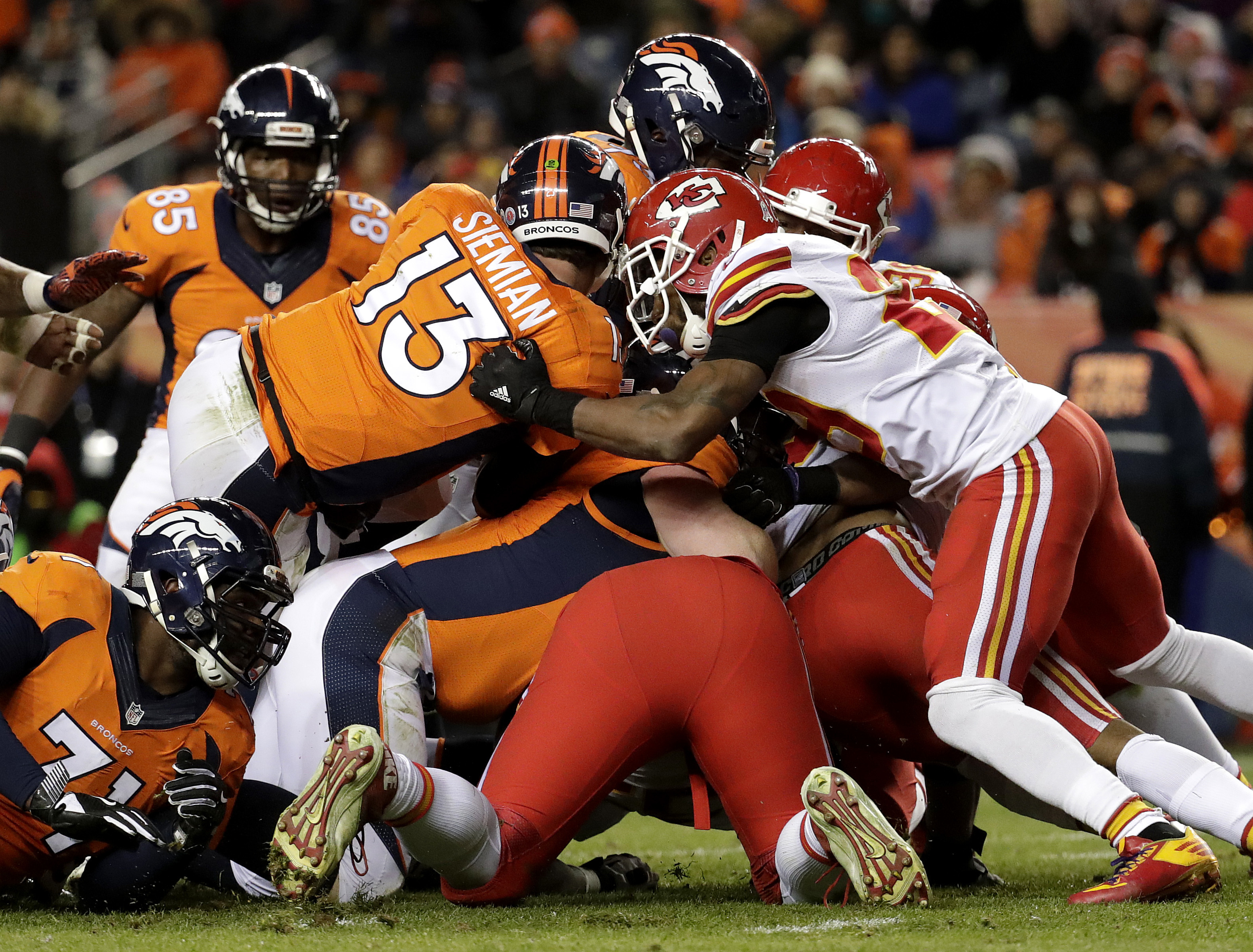 Denver Broncos quarterback Trevor Siemian (13) gets the first down on fourth and one as Kansas City Chiefs strong safety Eric Berry blocks during the second half of an NFL football game, Sunday, Nov. 27, 2016, in Denver. (AP Photo/Jack Dempsey)