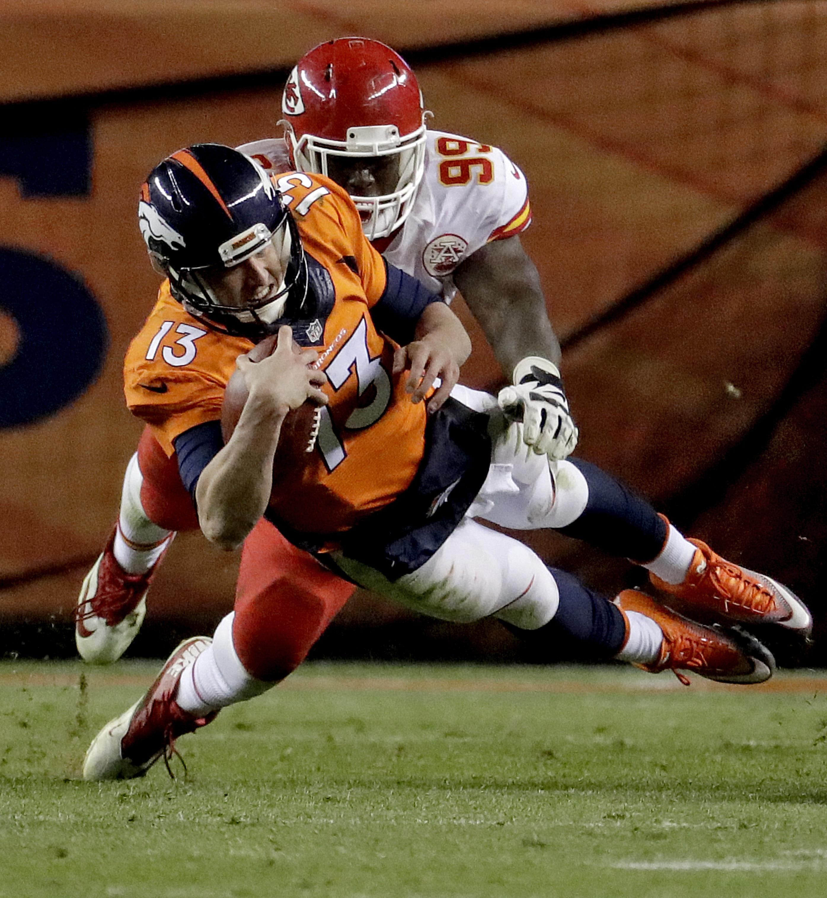 Denver Broncos quarterback Trevor Siemian (13) dives as Kansas City Chiefs defensive tackle Rakeem Nunez-Roches (99) pursues during the second half of an NFL football game, Sunday, Nov. 27, 2016, in Denver. (AP Photo/Jack Dempsey)