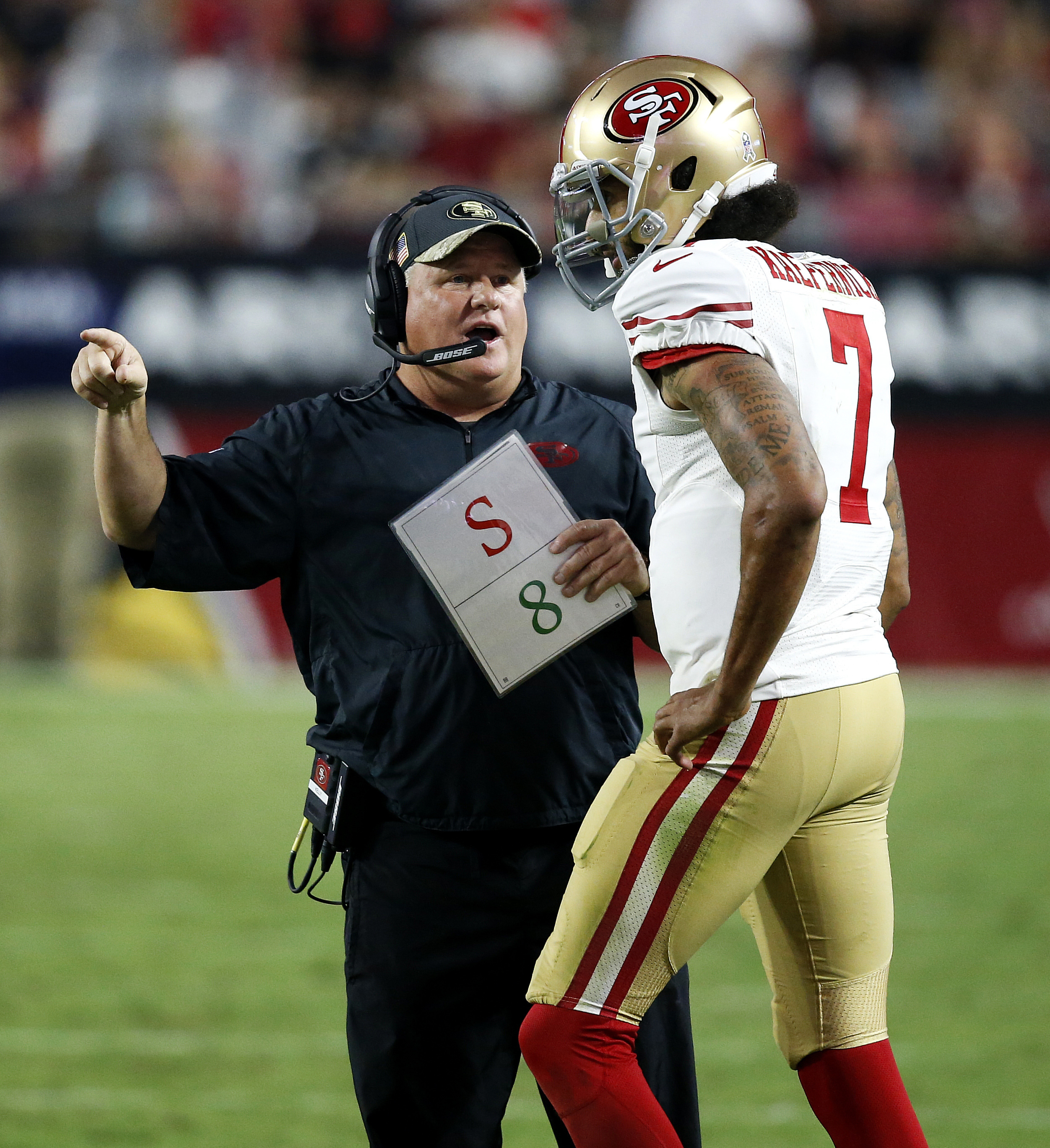 FILE - In this Sunday, Nov. 13, 2016, file photo, San Francisco 49ers head coach Chip Kelly talks with quarterback Colin Kaepernick (7) during the second half of an NFL football game in Glendale, Ariz. San Francisco will try to snap a franchise-record 10-