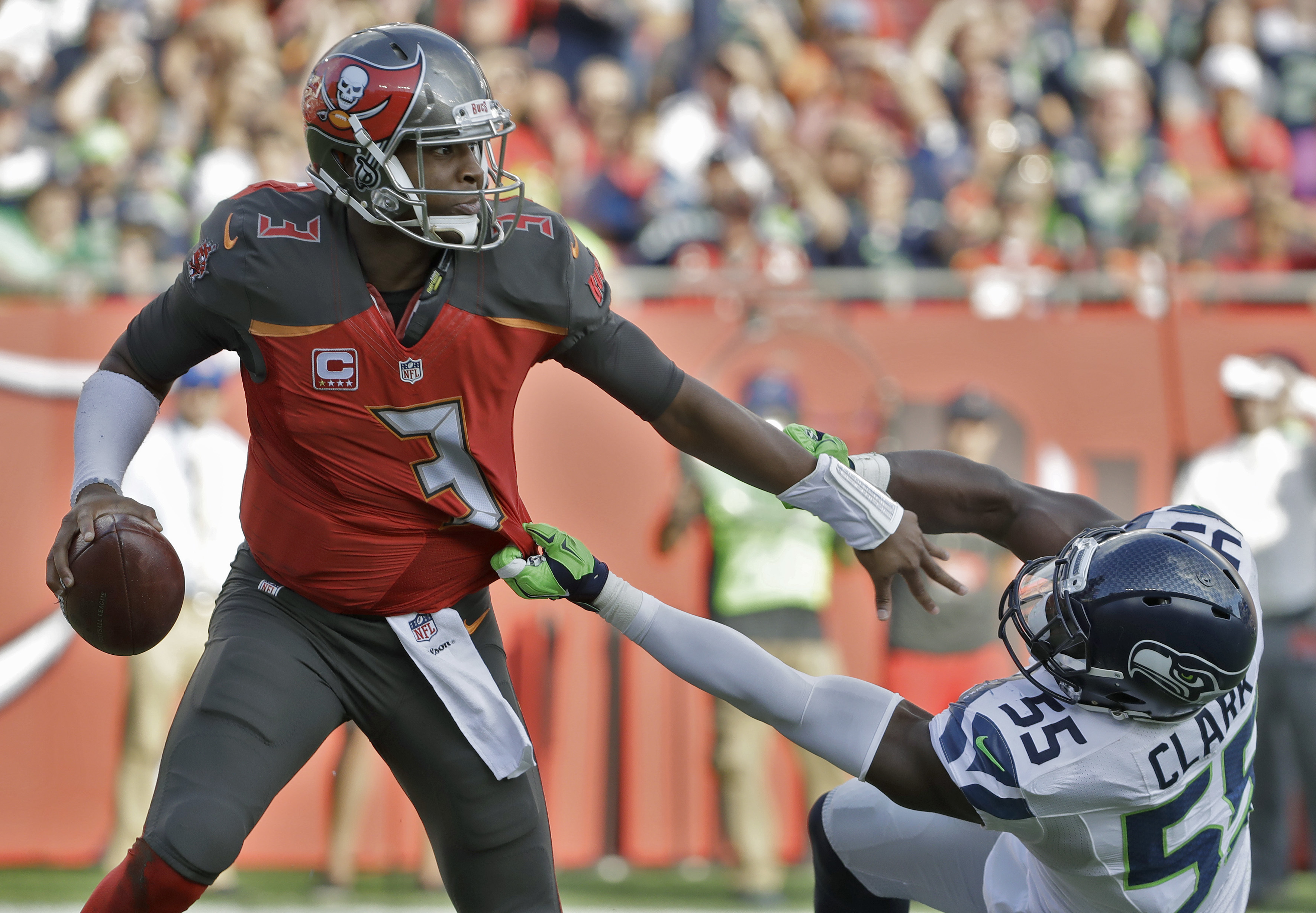 In this Sunday, Nov. 27, 2016, photo, Tampa Bay Buccaneers quarterback Jameis Winston (3) pushes off Seattle Seahawks defensive end Frank Clark (55) during the first quarter of an NFL football game in Tampa, Fla. The Buccaneers (6-5) have won three straig
