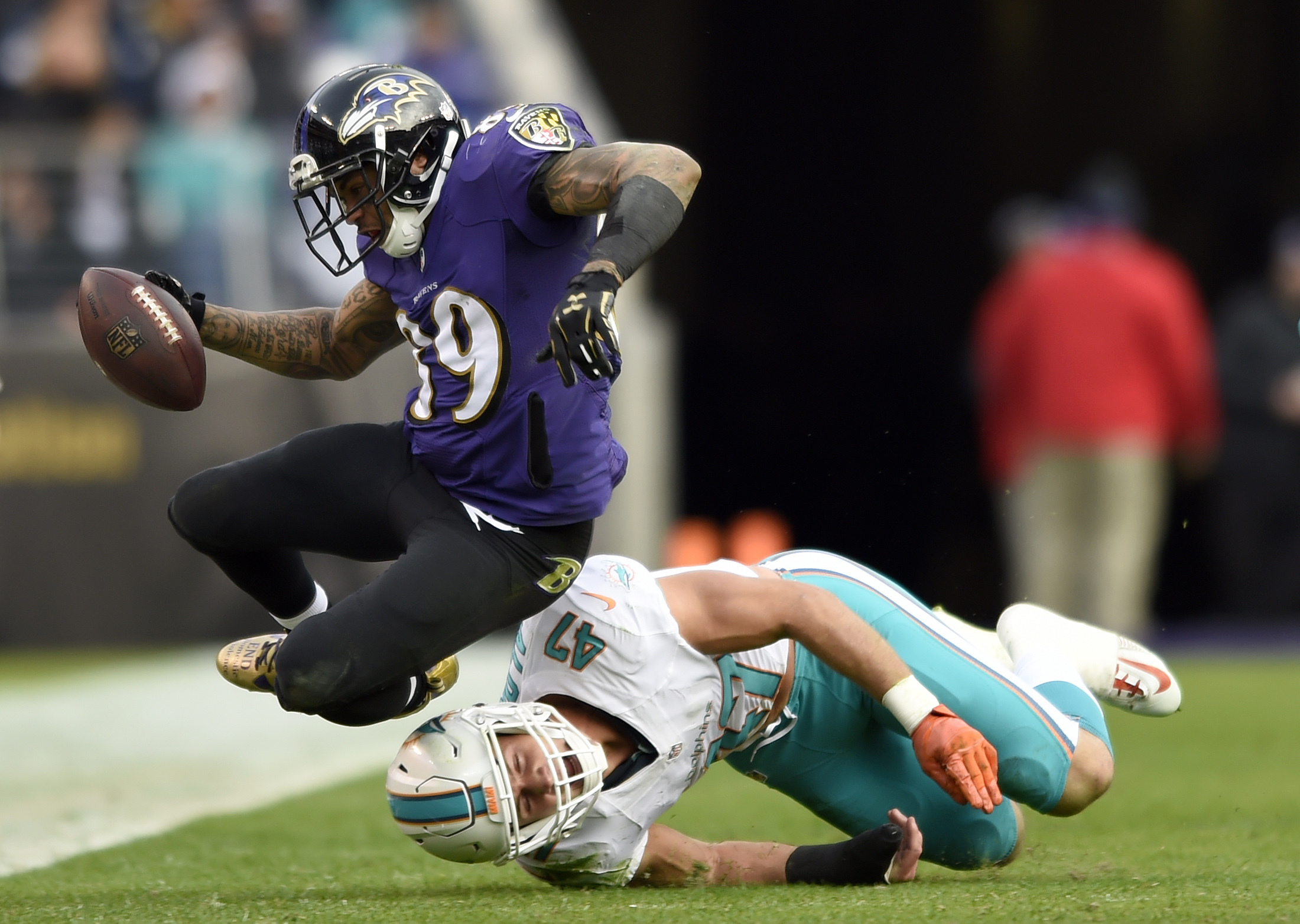 Baltimore Ravens wide receiver Steve Smith, top, falls over Miami Dolphins middle linebacker Kiko Alonso as he rushes the ball in the second half of an NFL football game, Sunday, Dec. 4, 2016, in Baltimore. (AP Photo/Gail Burton)