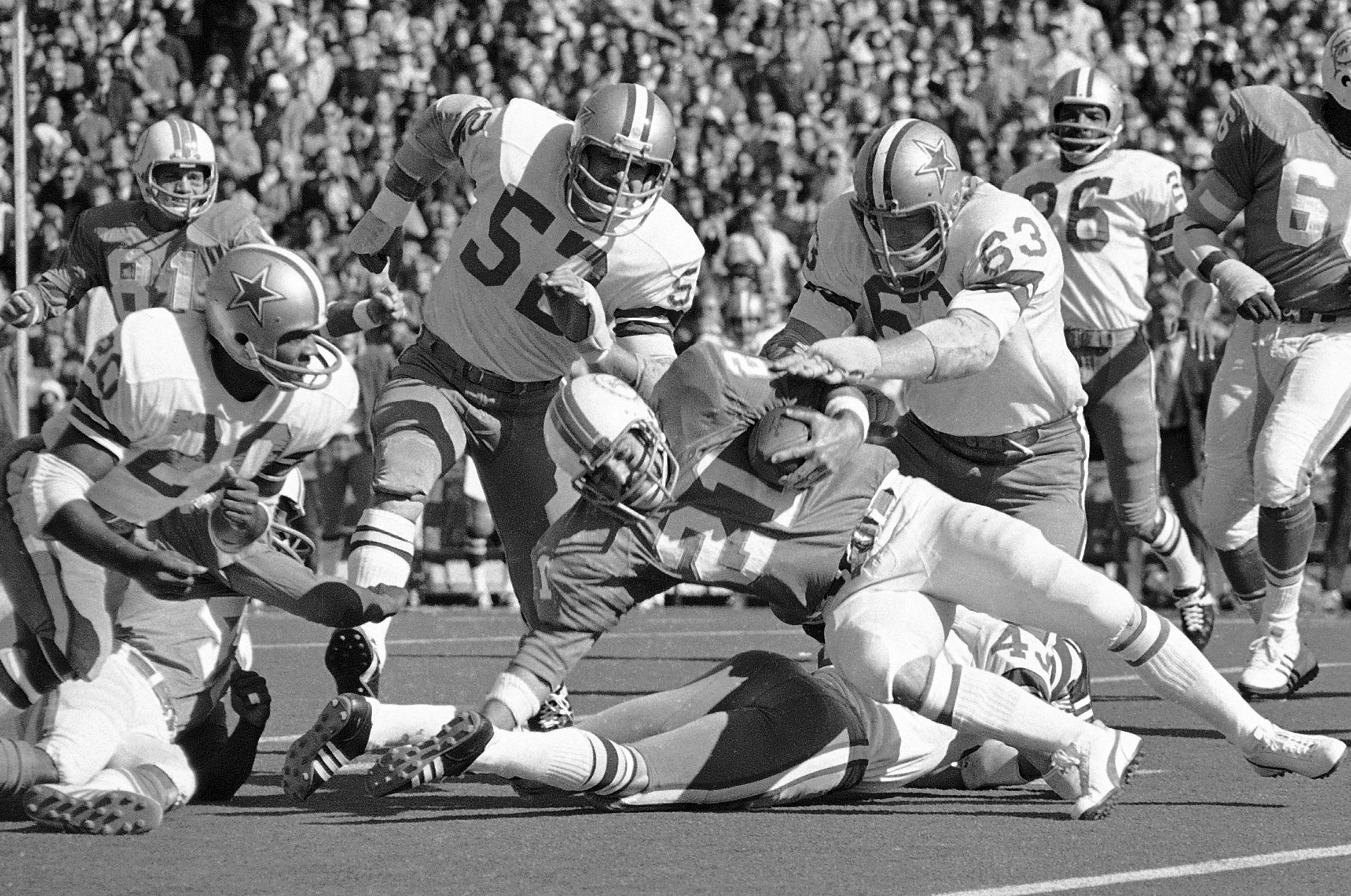 FILE - In this Jan. 16, 1972 file photo, Miami running back Jim Kiick (21) is brought down by Dallas tacklers after picking up a short game during first quarter of the Super Bowl football game in New Orleans. Also shown are Dallas Cowboys players Dave Edw