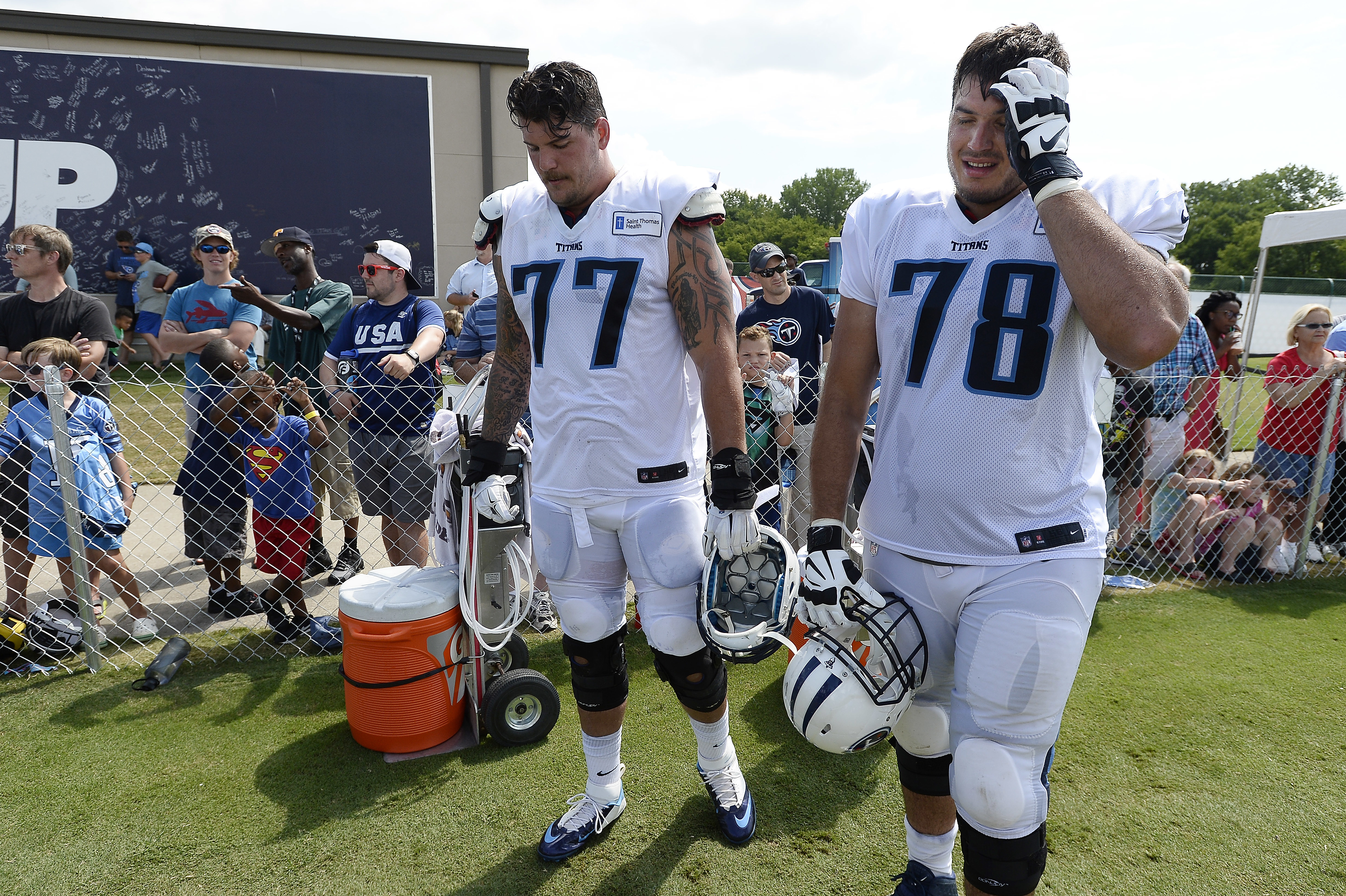 FILE - This Aug. 4, 2016 file photo shows Tennessee Titans tackles Taylor Lewan (77) and Jack Conklin (78) taking a break during NFL football training camp in Nashville, Tenn. The Tennessee Titans have done a much better job protecting quarterback Marcus