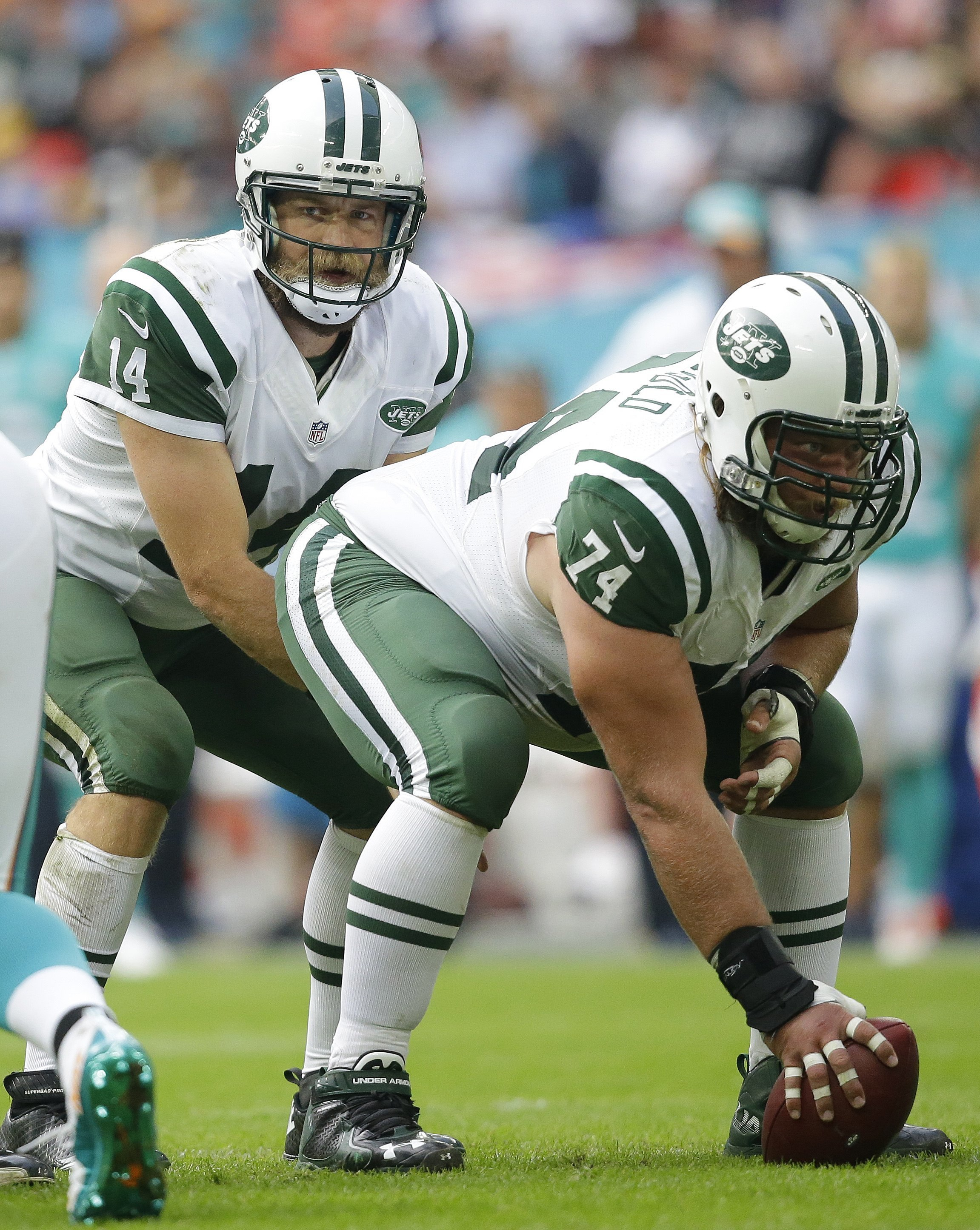 FILE - Sunday, Oct. 4, 2016 file photo, New York Jets' quarterback Ryan Fitzpatrick, left, prepares to take the ball from center Nick Mangold during an NFL football game against the Miami Dolphins at Wembley stadium in London. The New York Jets are placin