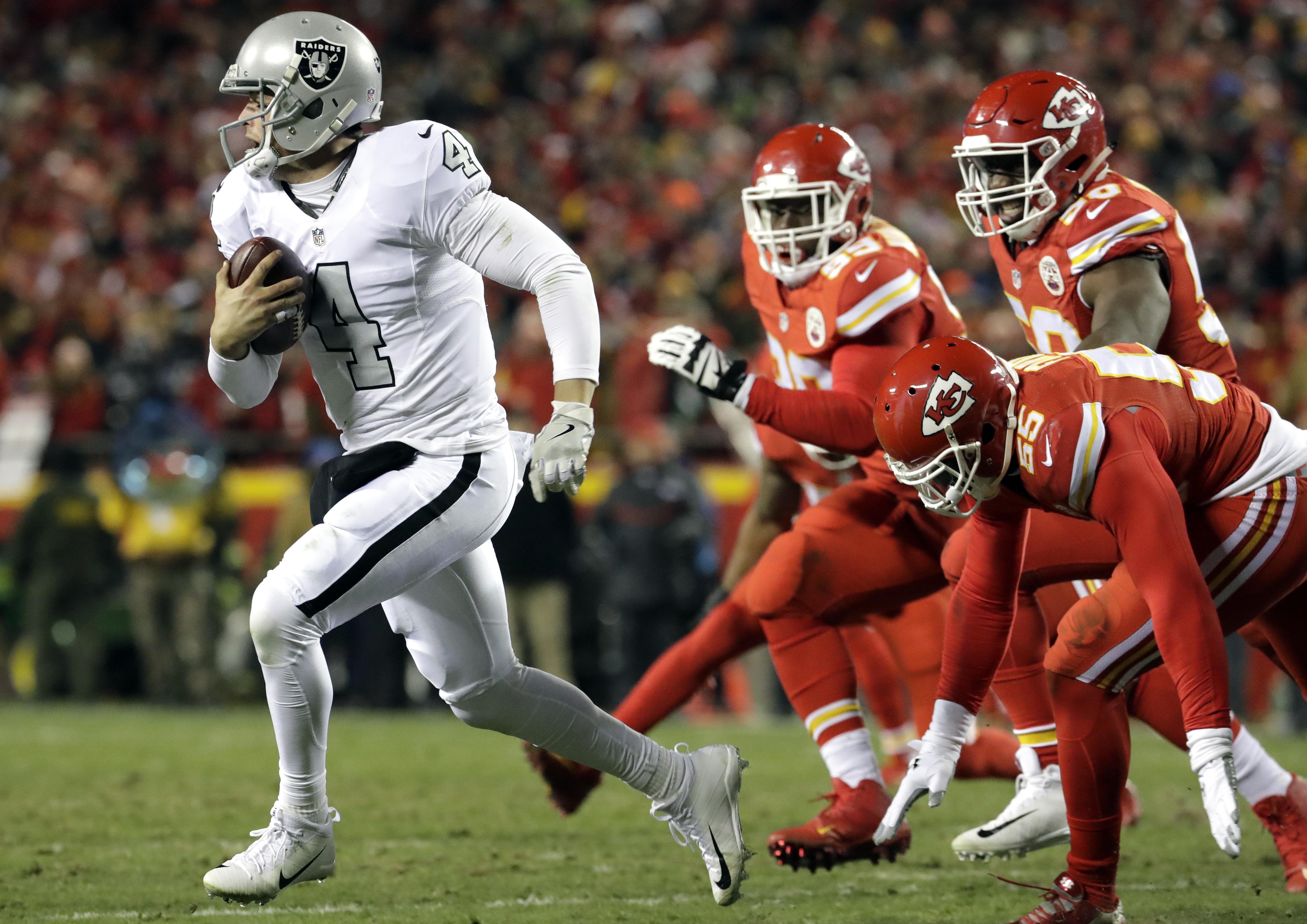 Oakland Raiders quarterback Derek Carr (4) runs away from Kansas City Chiefs linebacker Dee Ford (55), defensive lineman Rakeem Nunez-Roches (99) and linebacker Justin Houston (50) during the first half of an NFL football game in Kansas City, Mo., Thursda