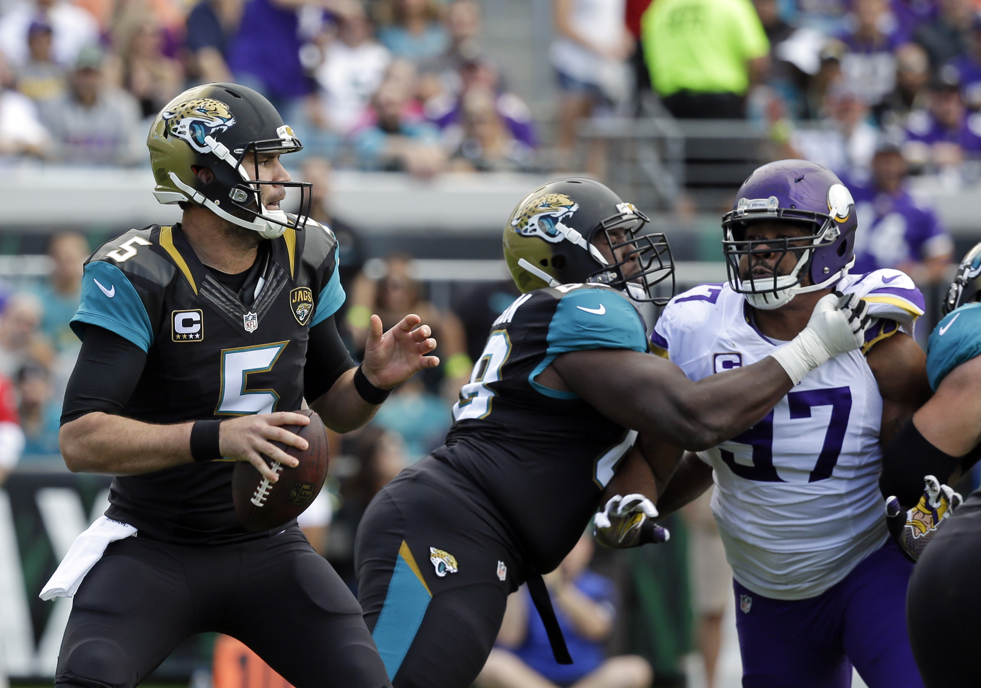 Jacksonville Jaguars quarterback Blake Bortles (5) looks for a receiver as tackle Kelvin Beachum, center, blocks Minnesota Vikings defensive end Everson Griffen (97) during the first half of an NFL football game, Sunday, Dec. 11, 2016, in Jacksonville, Fl