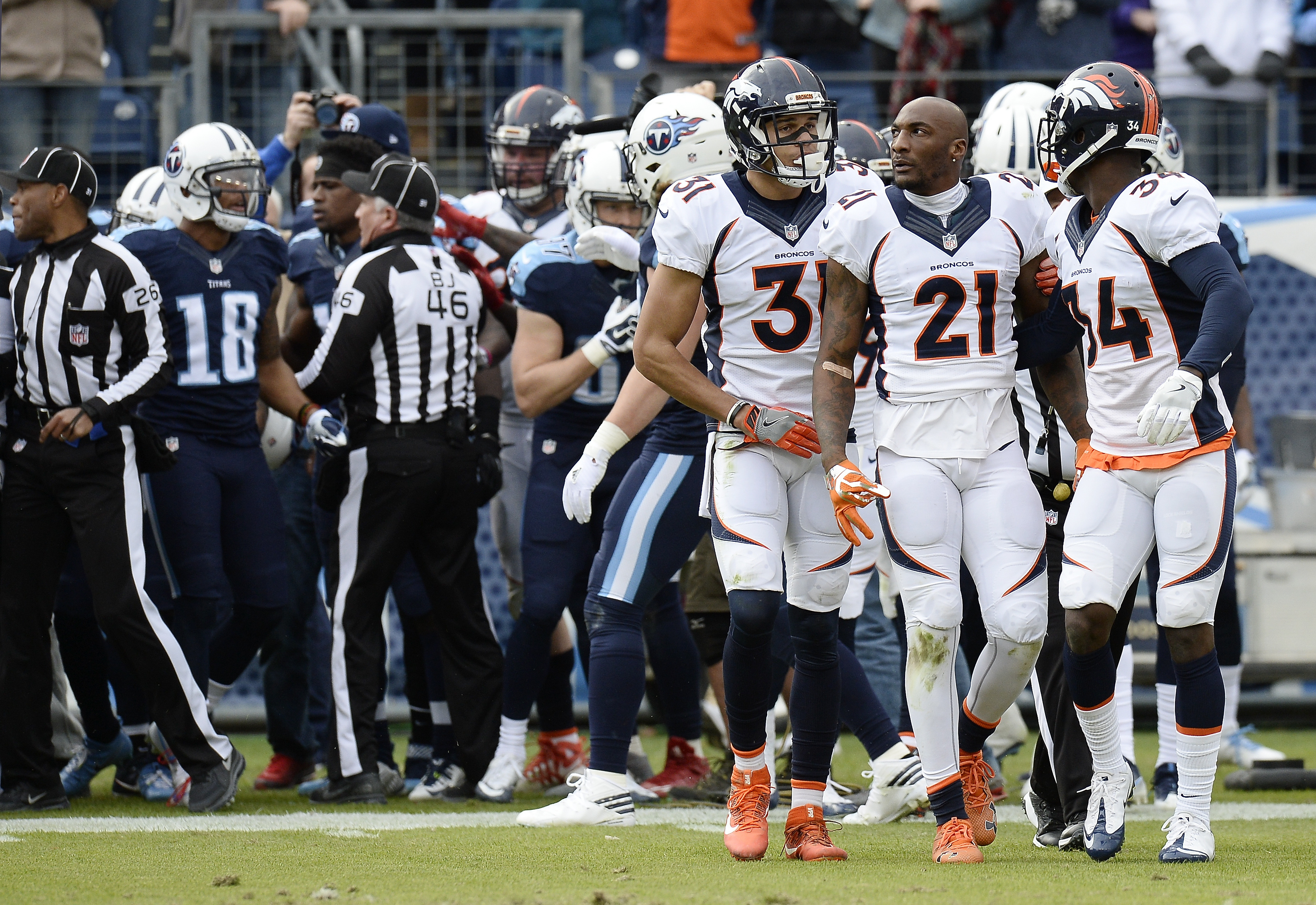 Denver Broncos cornerback Aqib Talib (21) walks to the bench with teammates Will Parks (34) and Justin Simmons (31) after Talib was involved in a scuffle with Tennessee Titans players in the first half of an NFL football game Sunday, Dec. 11, 2016, in Nas