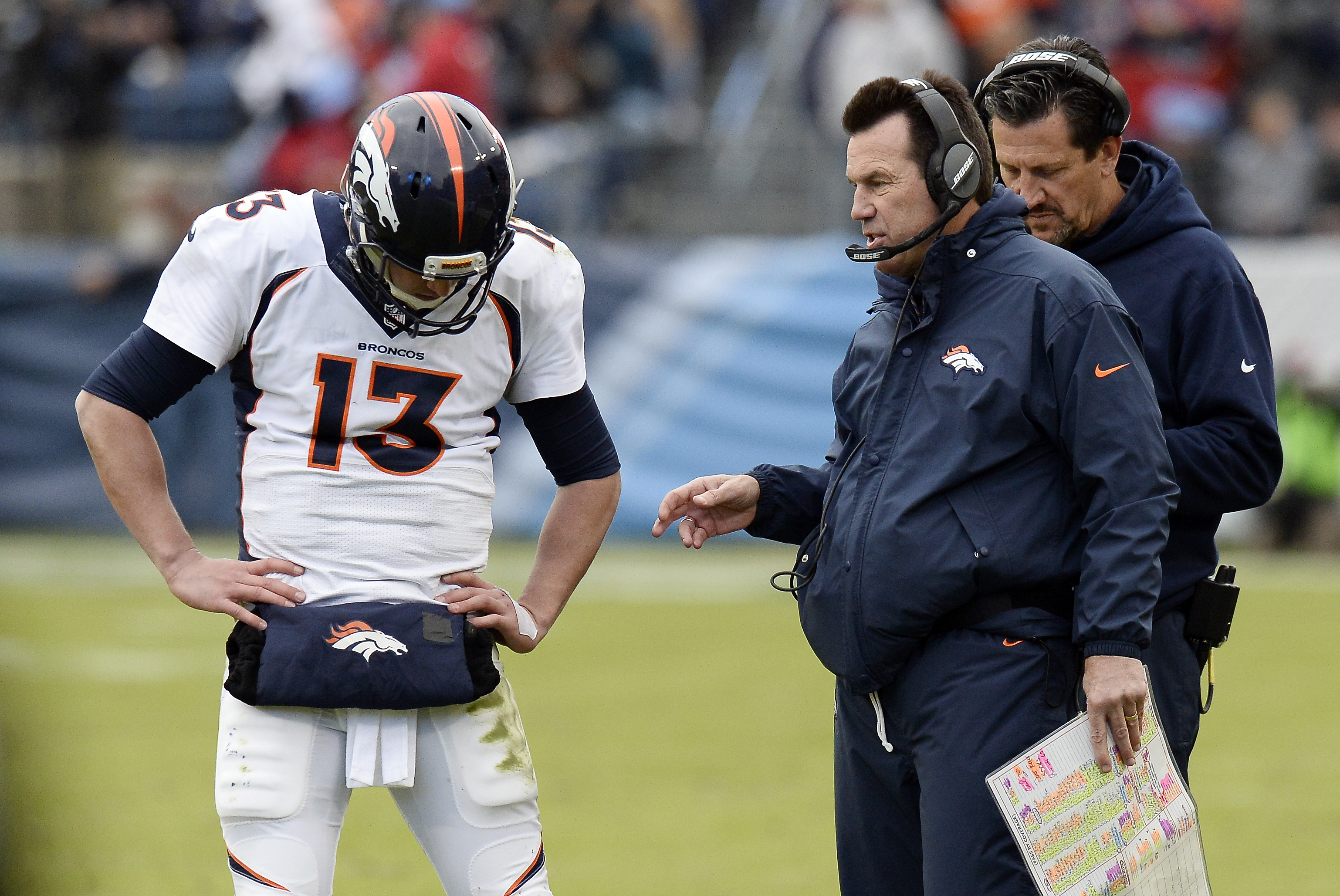 Denver Broncos head coach Gary Kubiak, center, talks with quarterback Trevor Siemian (13) in the second half of an NFL football game against the Tennessee Titans Sunday, Dec. 11, 2016, in Nashville, Tenn. (AP Photo/Mark Zaleski)