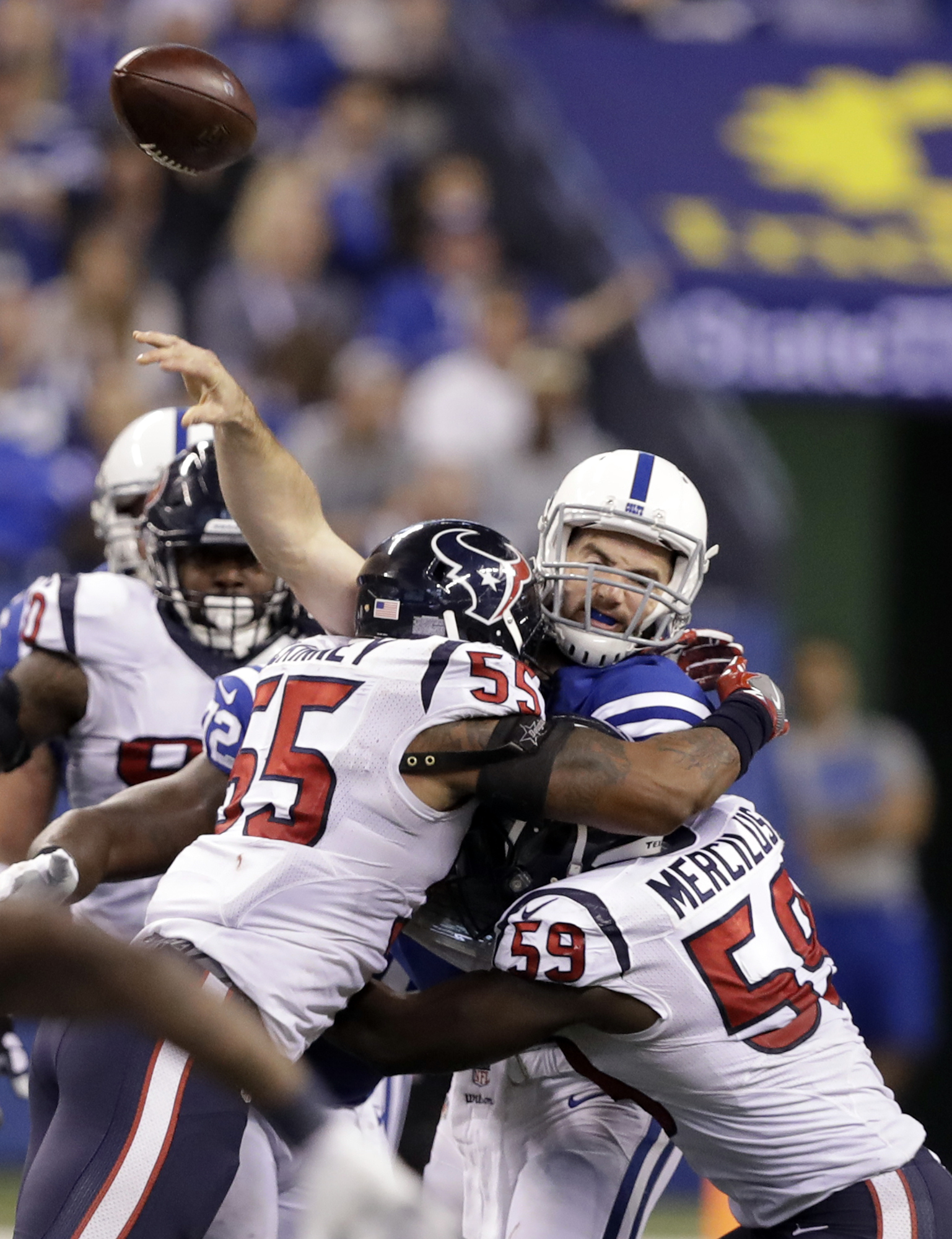 Indianapolis Colts quarterback Andrew Luck, center, is hit as he throws by Houston Texans linebacker Benardrick McKinney (55) and linebacker Whitney Mercilus (59) during the second half of an NFL football game, Sunday, Dec. 11, 2016, in Indianapolis. (AP