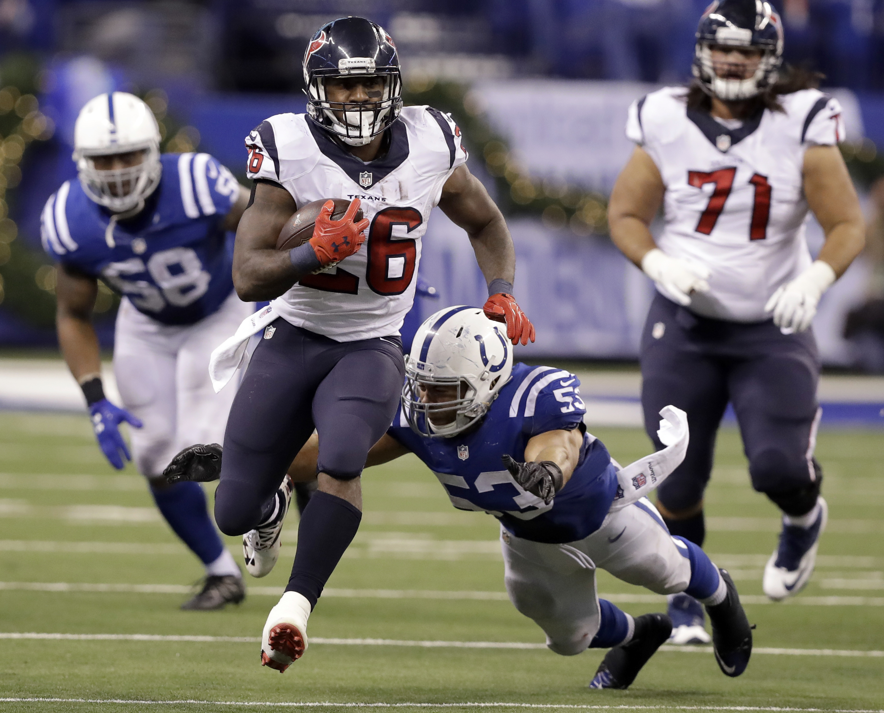 Houston Texans running back Lamar Miller (26) runs with the ball as Indianapolis Colts linebacker Edwin Jackson (53) and linebacker Trent Cole defend during the second half of an NFL football game, Sunday, Dec. 11, 2016, in Indianapolis. (AP Photo/Darron