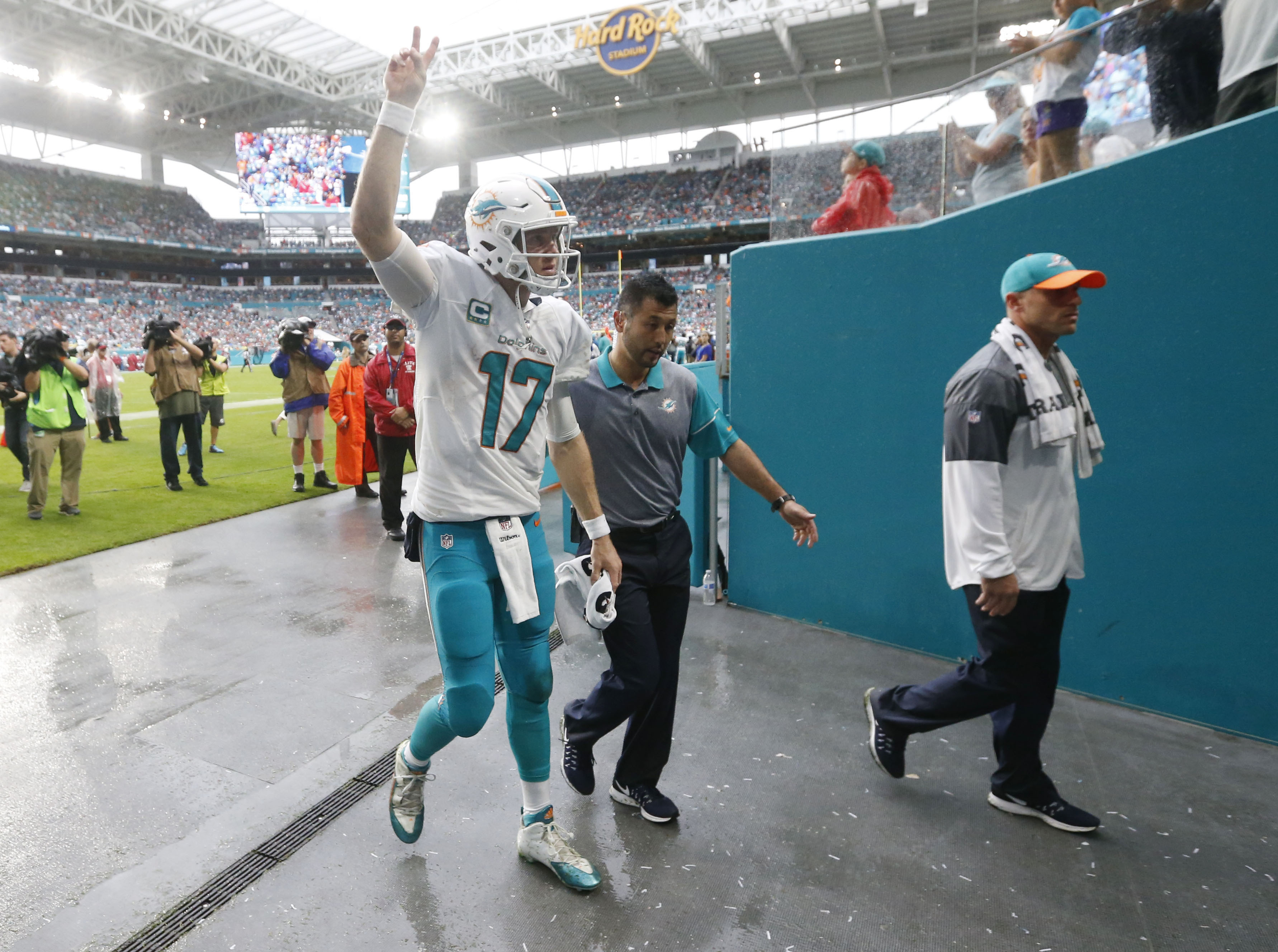 Miami Dolphins quarterback Ryan Tannehill (17) waves to fans as he is escorted off the field after he was injured, during the second half of an NFL football game against the Arizona Cardinals, Sunday, Dec. 11, 2016, in Miami Gardens, Fla. (AP Photo/Wilfre