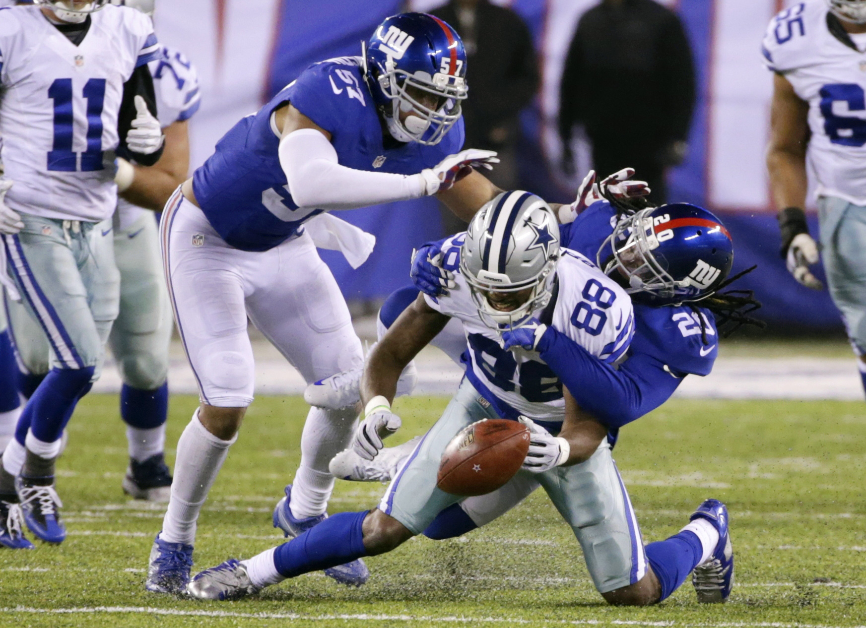 Dallas Cowboys wide receiver Dez Bryant (88) fumbles the ball during the second half of an NFL football game as New York Giants' Janoris Jenkins (20) and Keenan Robinson (57) defend Sunday, Dec. 11, 2016, in East Rutherford, N.J. (AP Photo/Seth Wenig)