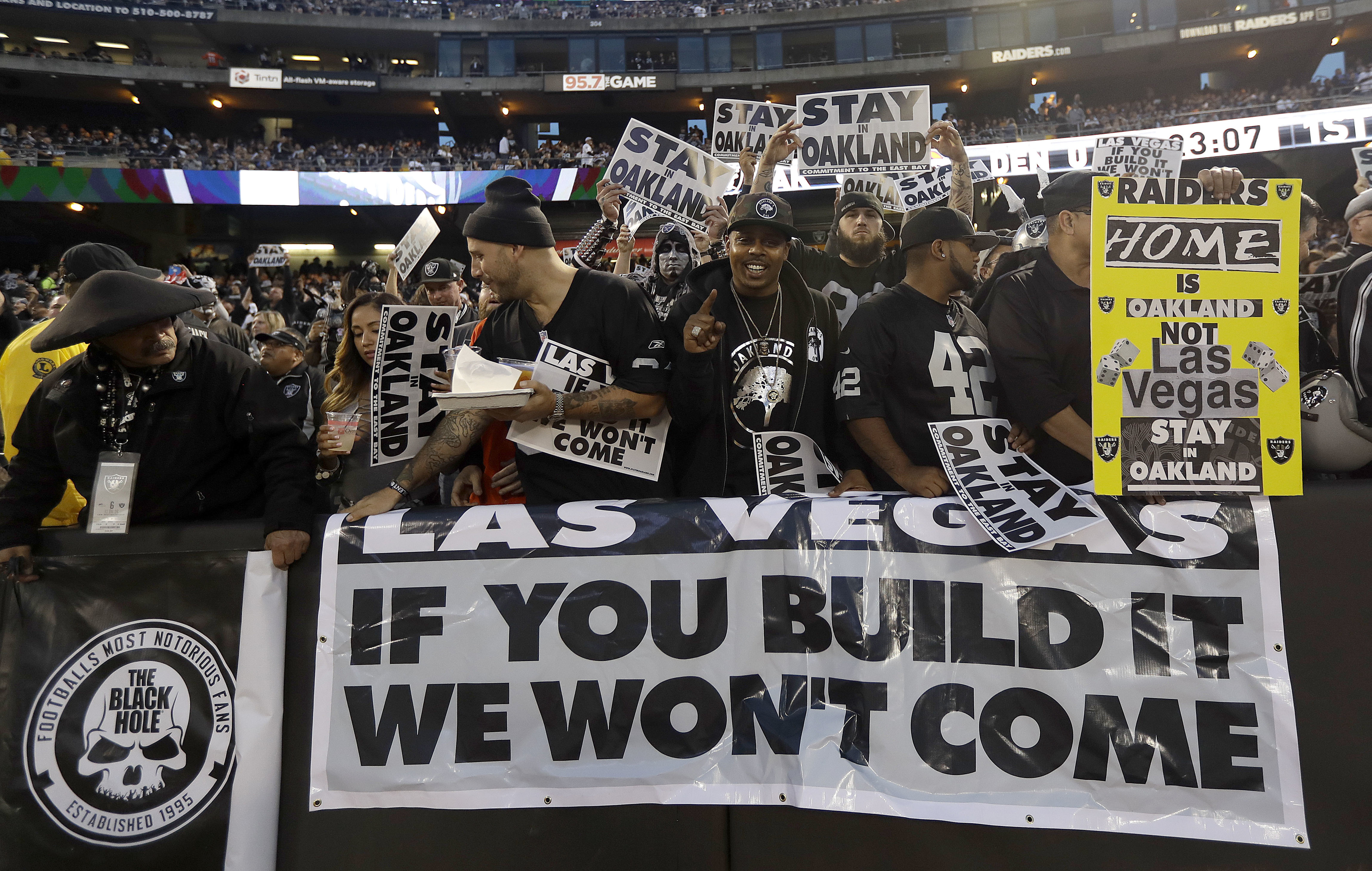 FILE - In this Nov. 6, 2016, file photo, Oakland Raiders fans hold up signs about the team's possible move to Las Vegas during an NFL football game between the Raiders and the Denver Broncos in Oakland, Calif. City and county officials are expected to vot